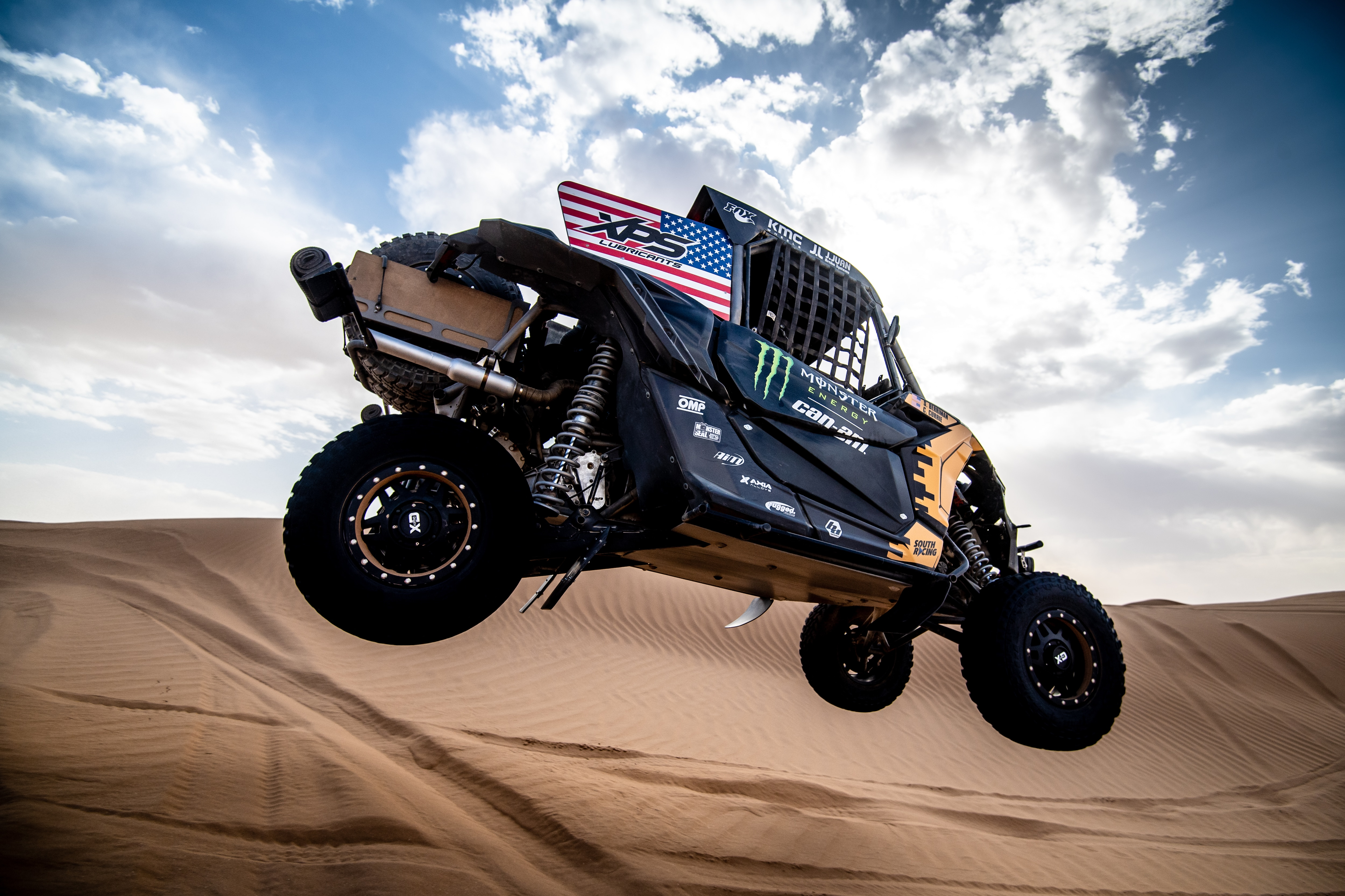 Man driving a Maverick X3 in desert dunes