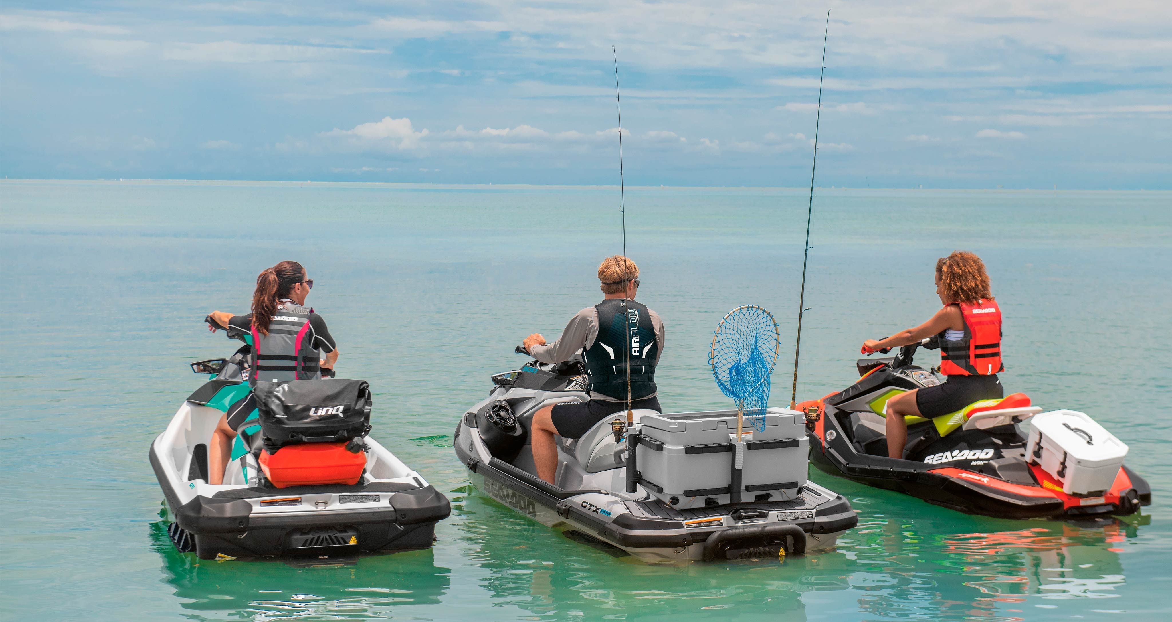 Three friends  with fishing equipment riding their Sea-doo personal watercraft