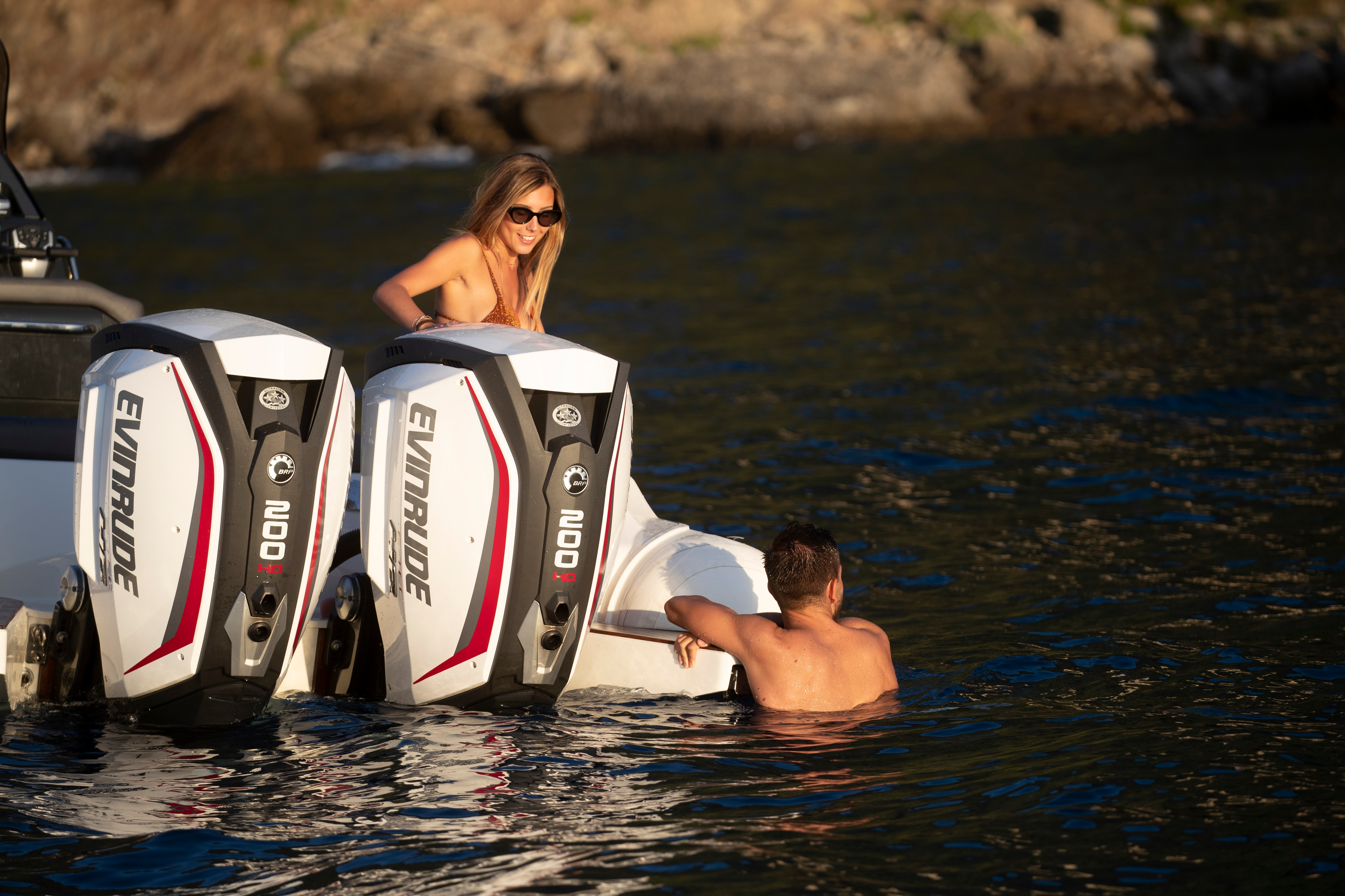 A man and a woman swimming close to a boat yielding an Evinrude motor