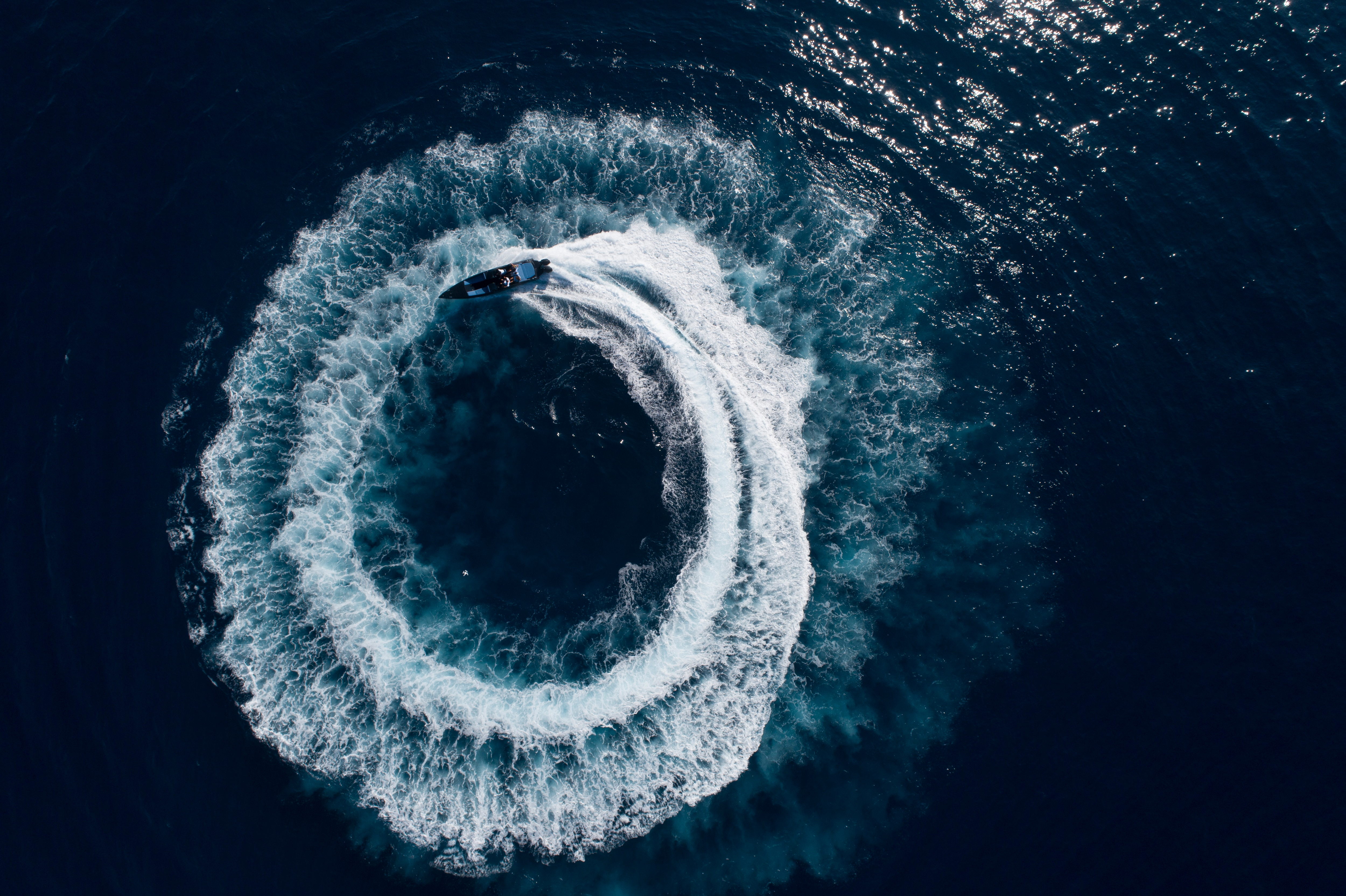 Bird view of a boat doing large circles in the watter