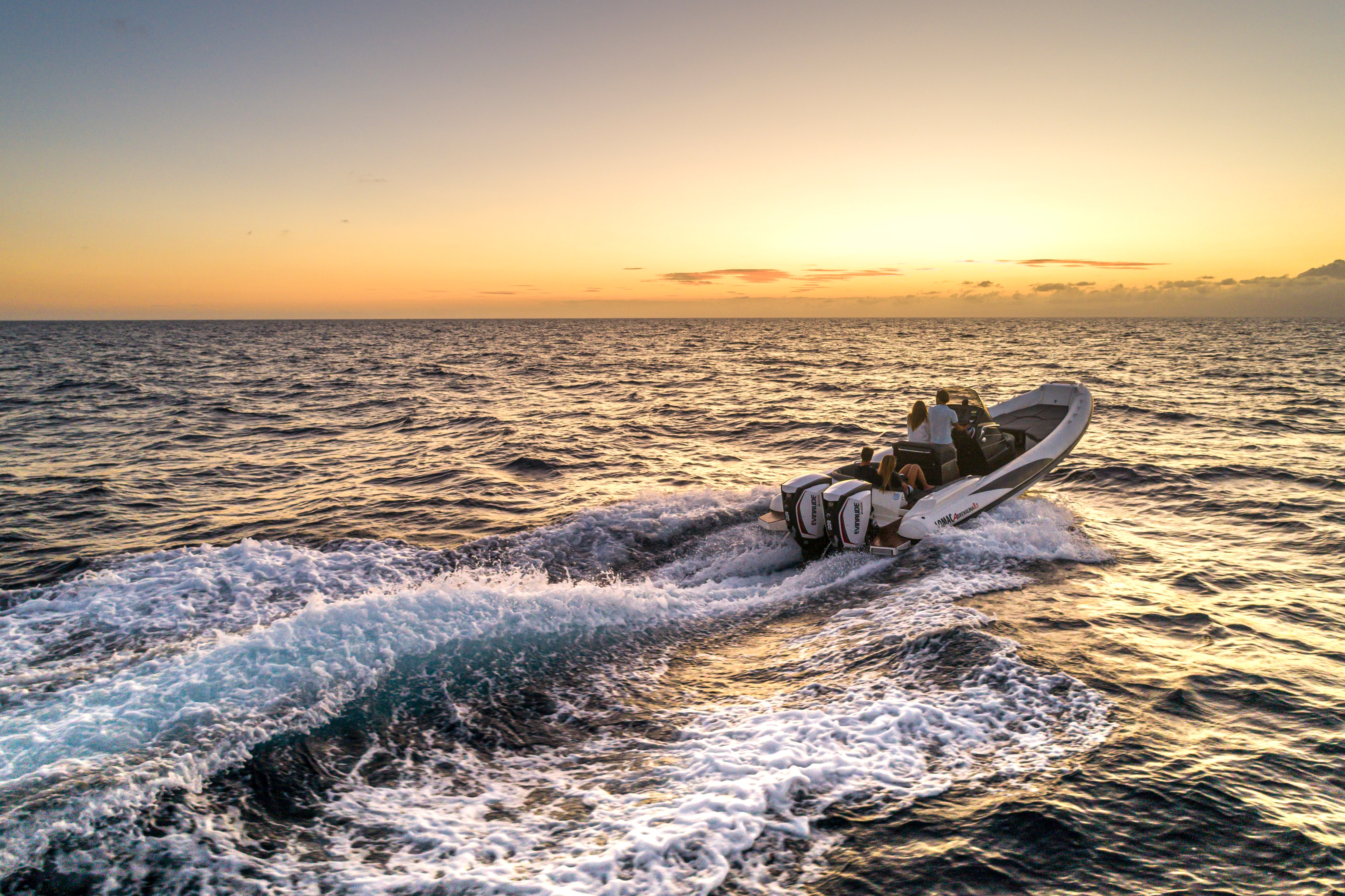 Wide angle shot of a boat yielding an Evinrude motor diving towards the sunset