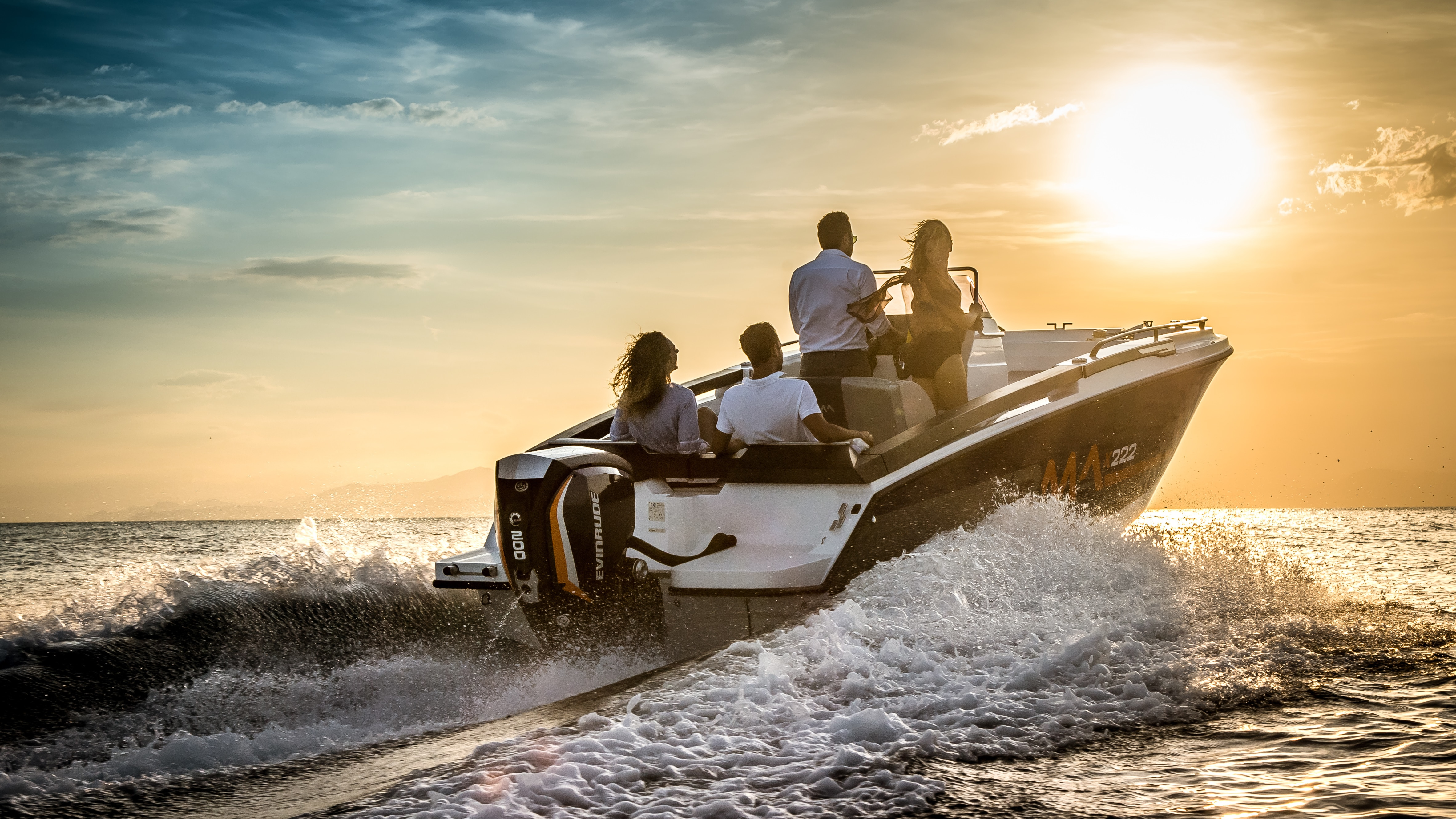 Four people on a boat yielding an Evinrude motor driving towards the sunset