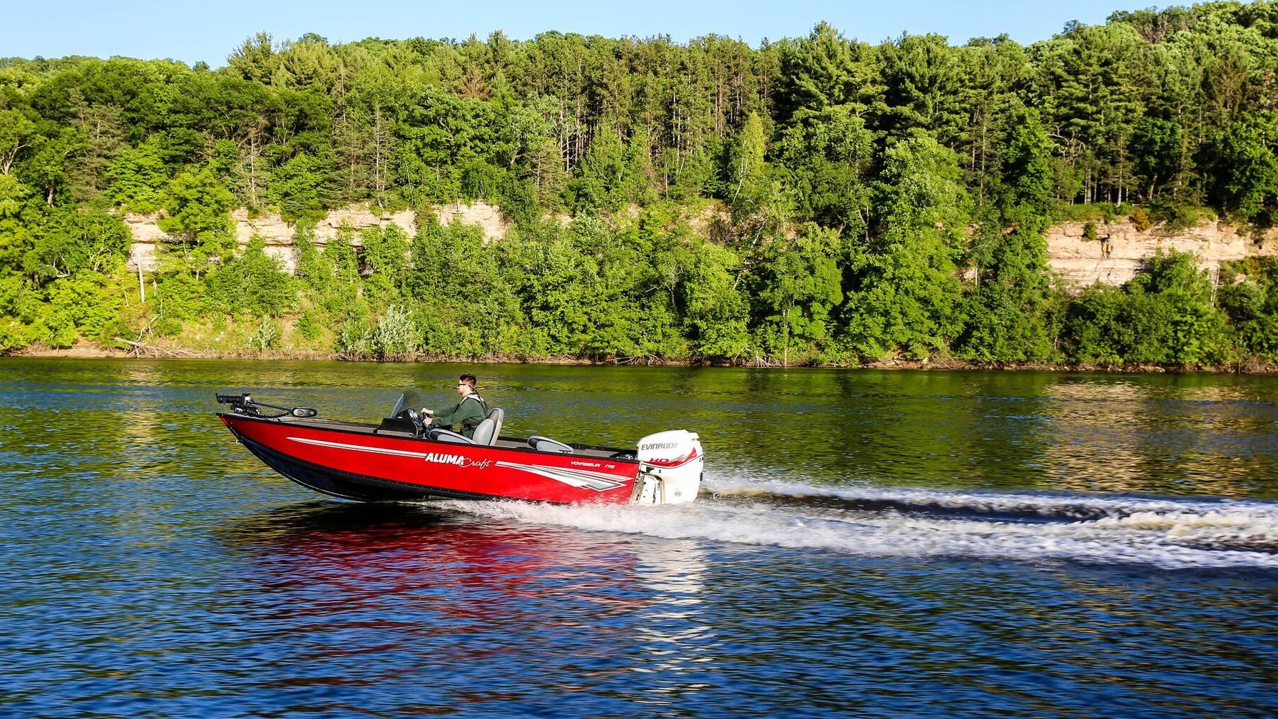 Man driving his Alumacraft boat with an Evinrude motor in a lake