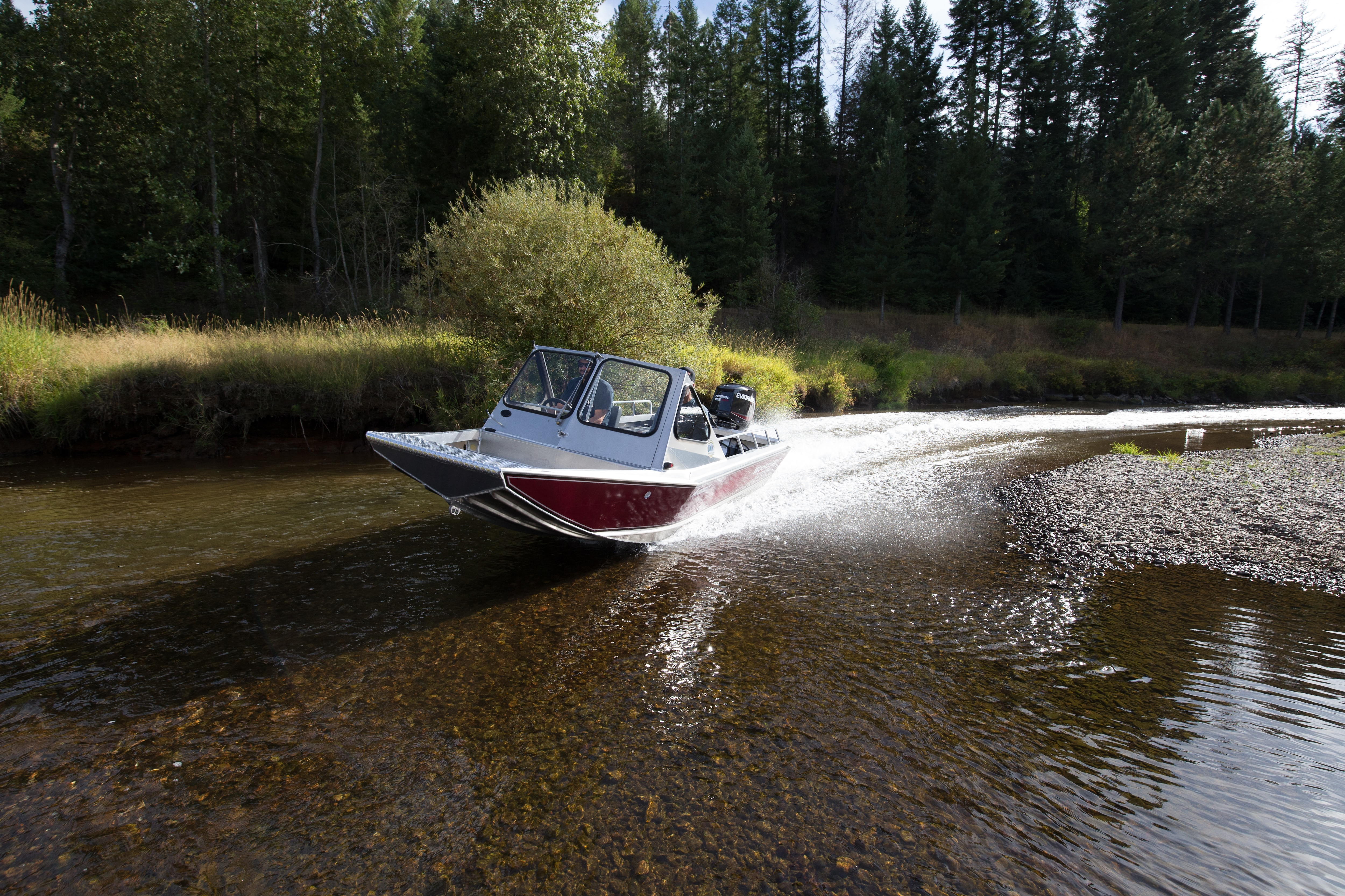 Man driving small boat across shallow water