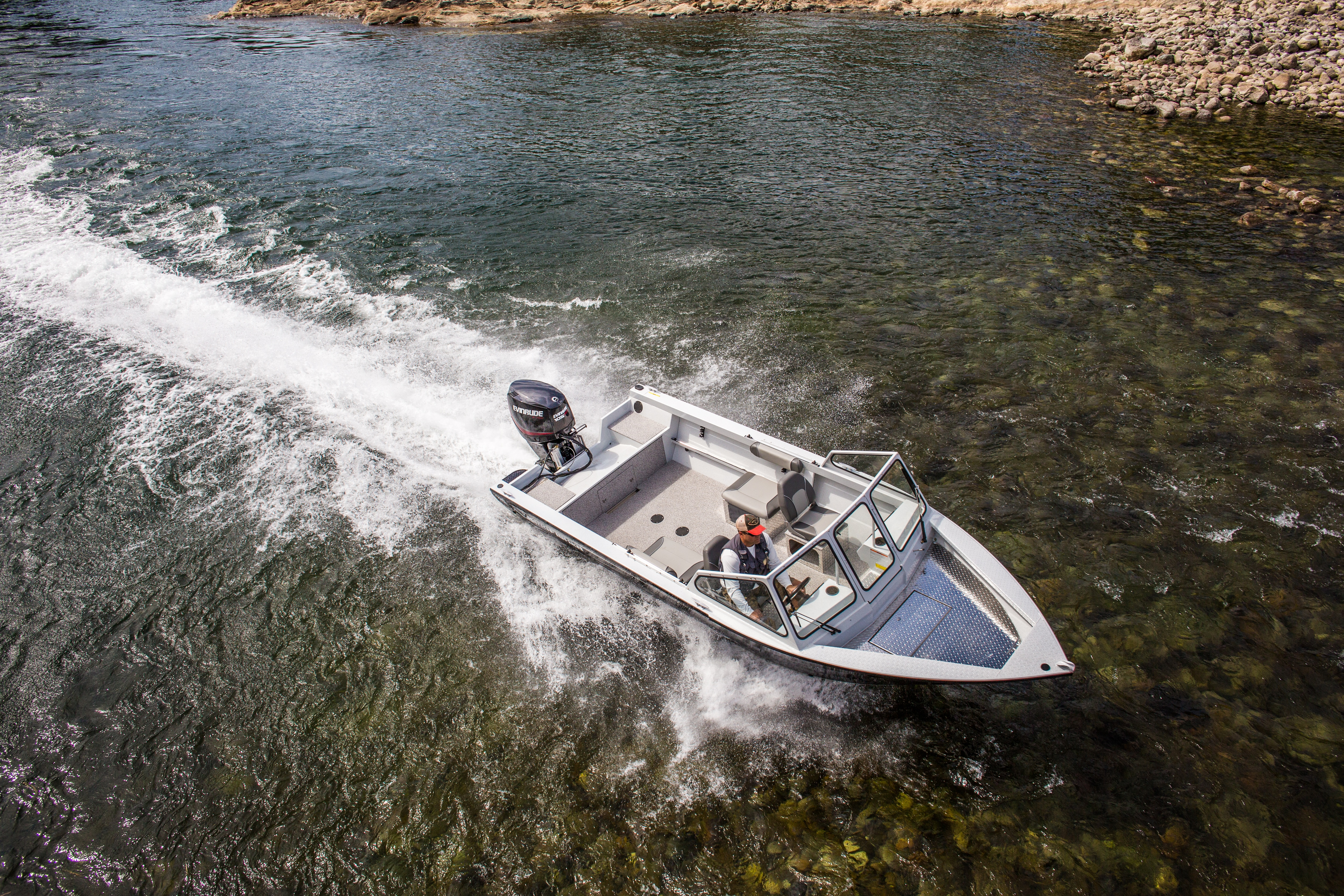 Man driving a Evinrude motorboat in shallow water