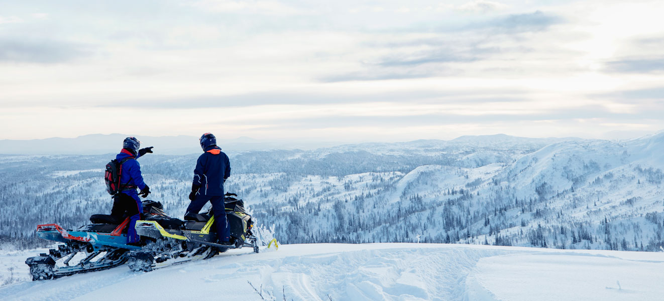 Two men sitting on their Lynx Snowmobile and looking at the horizon