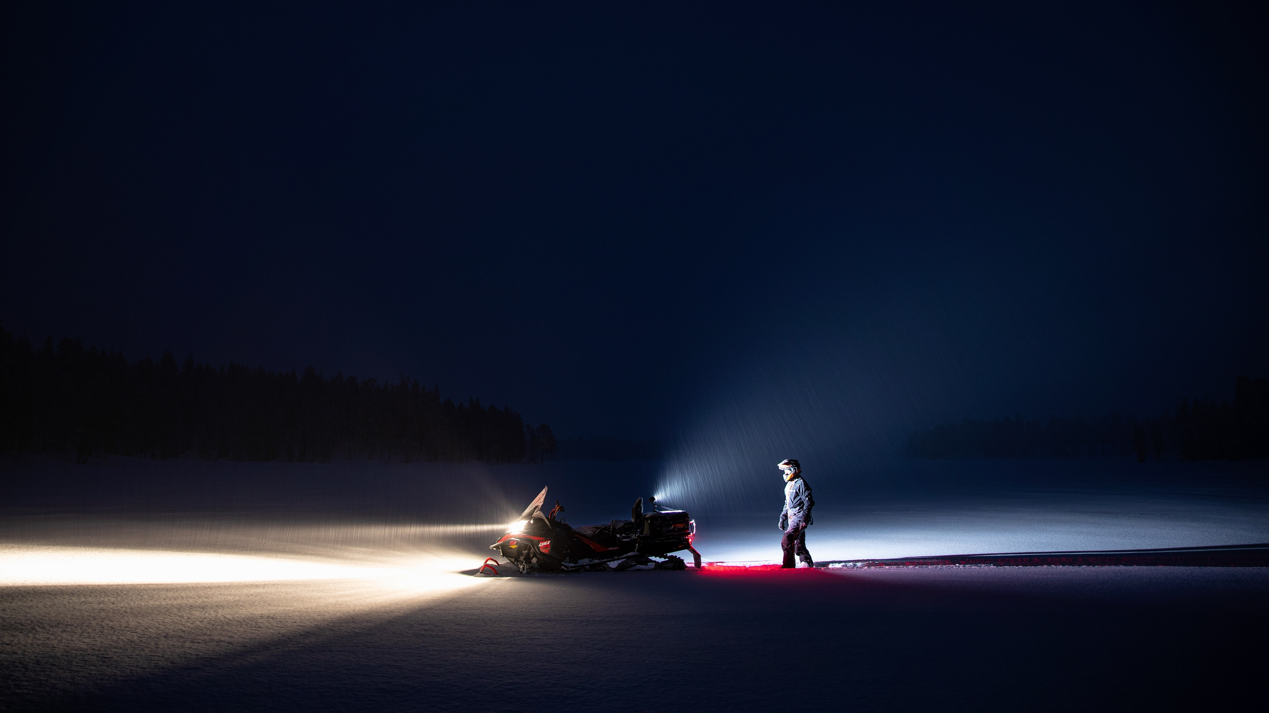 Wide shot of a man walking towards his Lynx 2021 Snowmobile at night