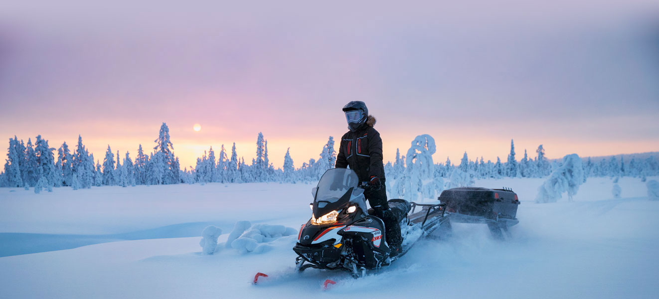 A man is riding his Lynx 49 Ranger Snowmobile Model on a snowy road at sunset
