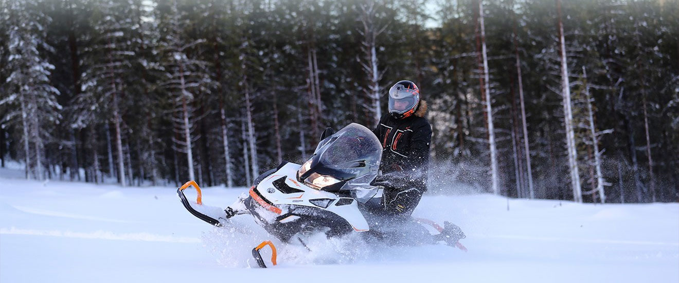 Man driving his 69 Ranger snowmobile through snow