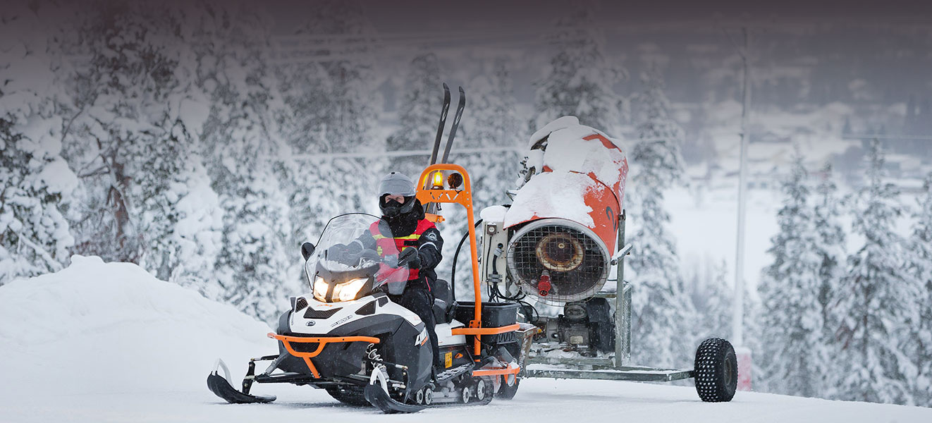 Man towing a snow cannon with his Lynx 69 Ranger
