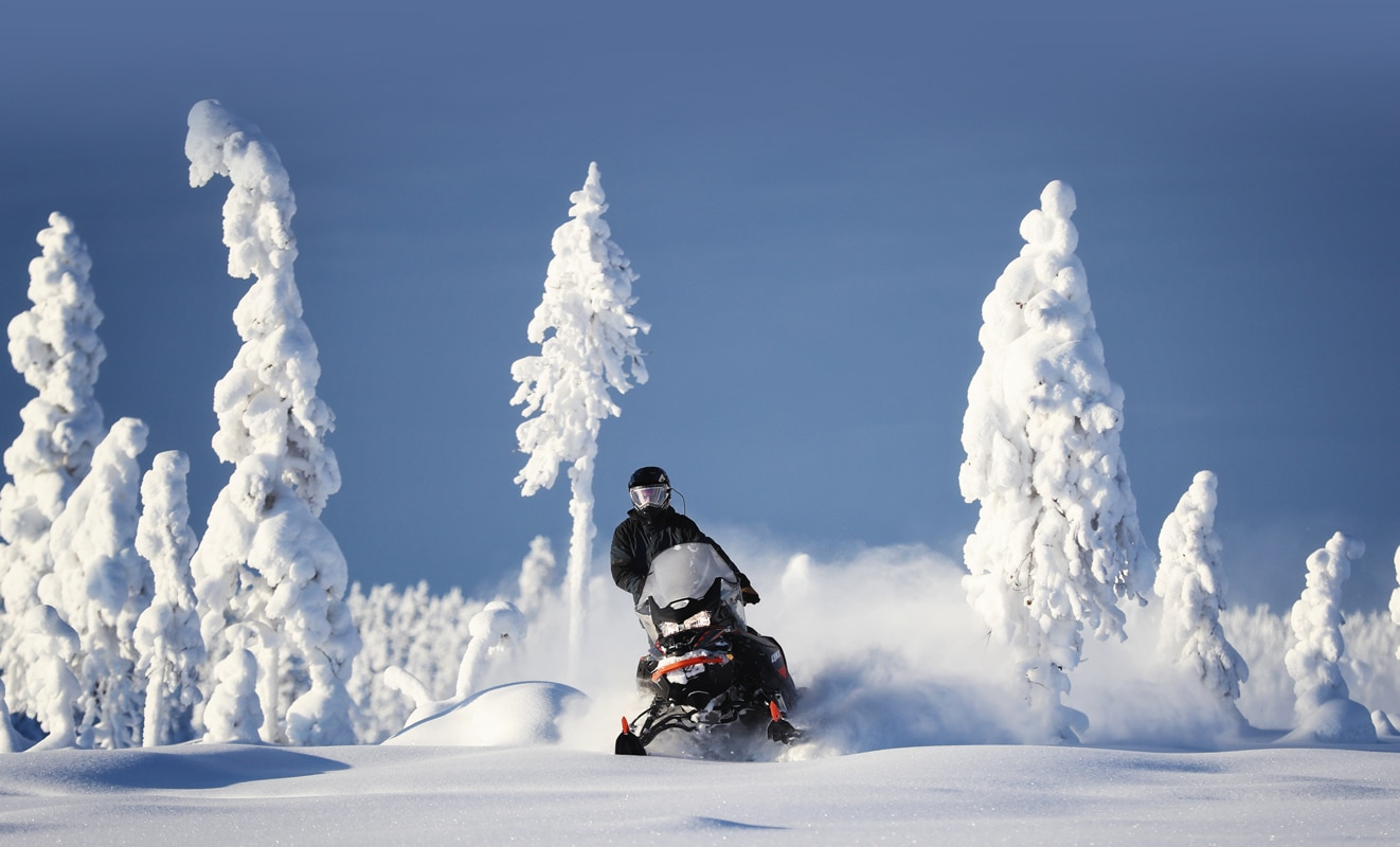 A man is riding his Lynx Commander Snowmobile Model throught the snowy forest under the sun