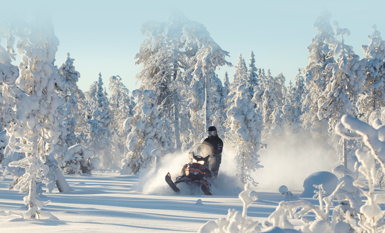 A man is riding his Lynx Commander Snowmobile Model throught the snowy forest