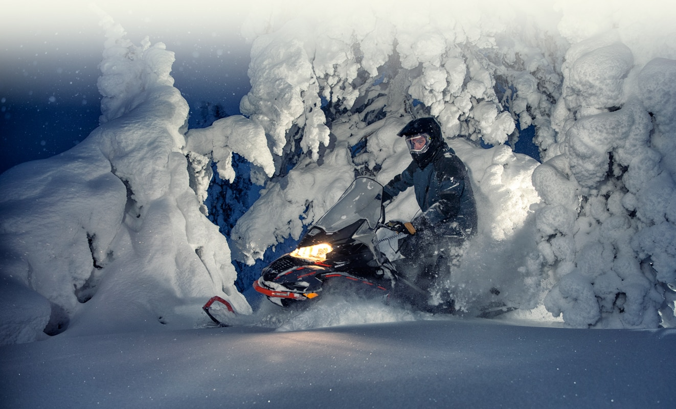 A man is driving his Lynx Commander Snowmobile Model throught the snowy forest during the night