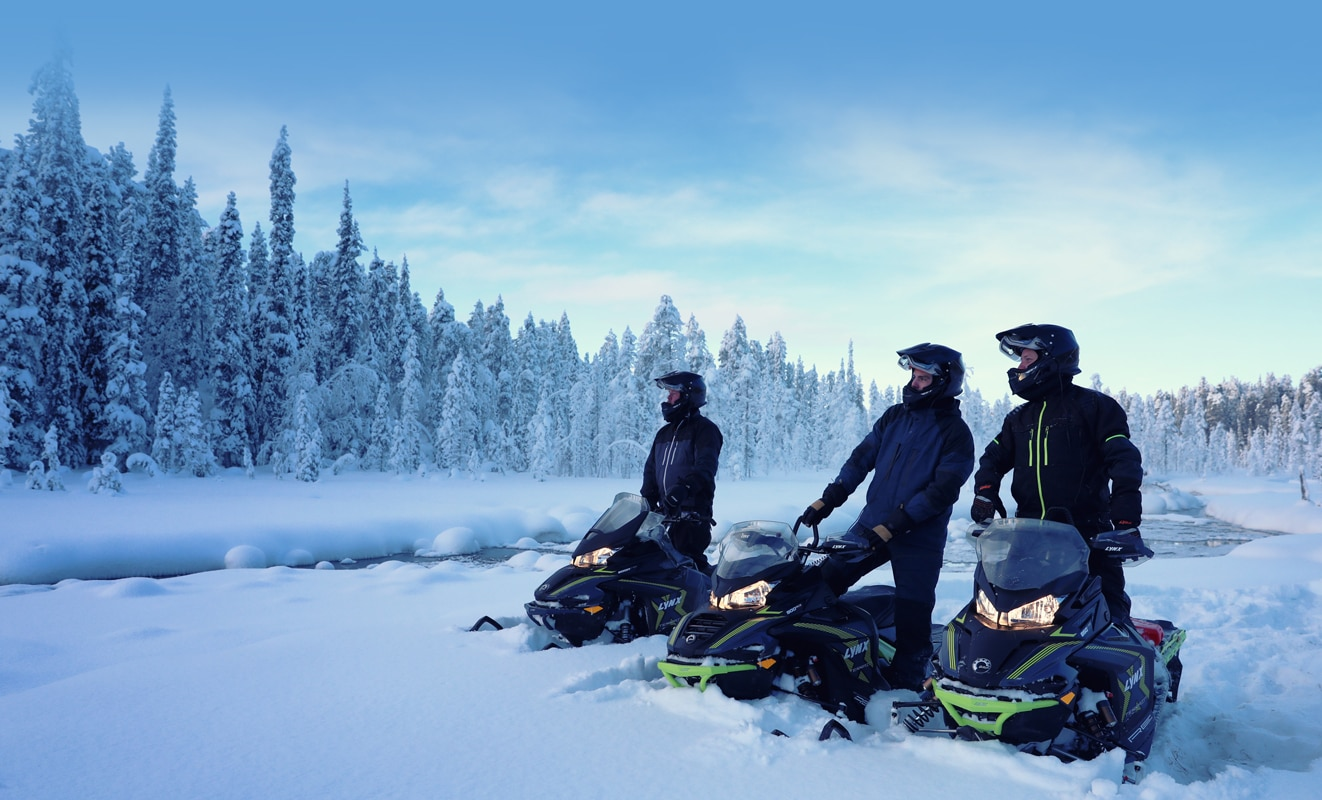 3 men are watching the view of the snow-covered forest, they each have a Lynx Xterrain Snowmobile Model