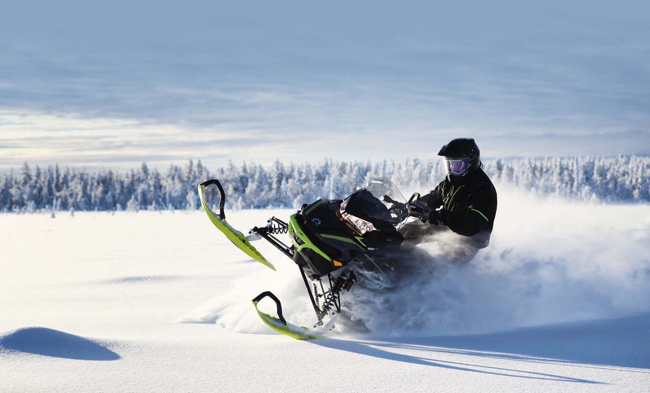 A man drifts in the snow with his Lynx Xterrain Snowmobile Model