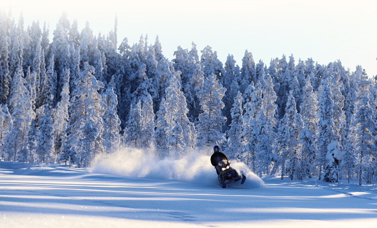 A man drifts in the snow with his Lynx Xterrain Snowmobile Model in the middle of the snowy forest
