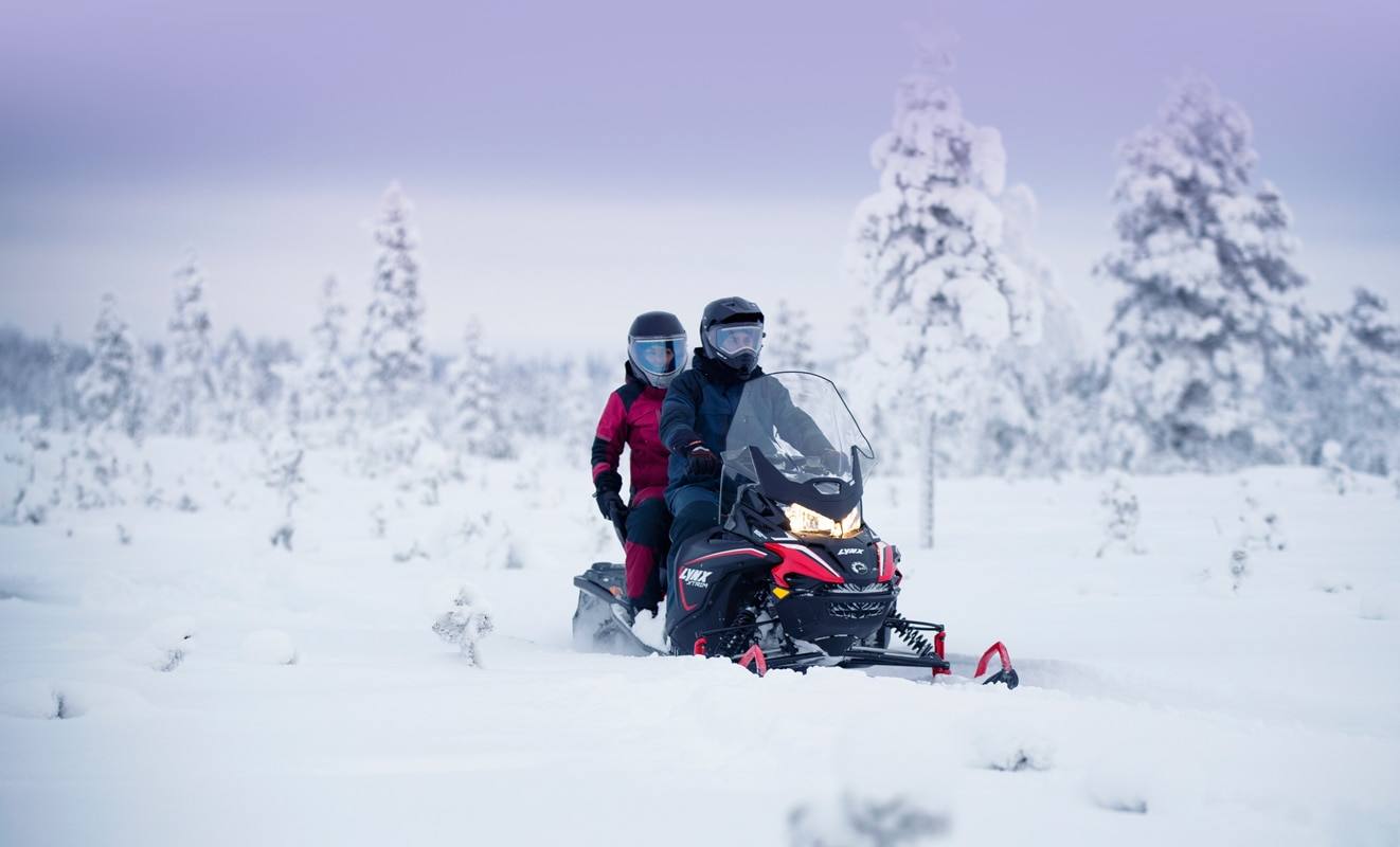 A couple is riding a Lynx Xtrim Snowmobile Model on a snowy road
