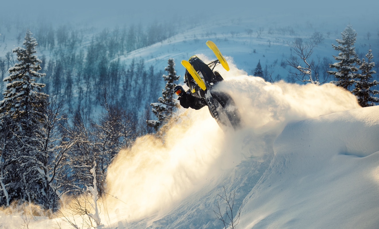 A man is doing a backflip with his Lynx Xtrim Snowmobile Model on the top of a snowy hill