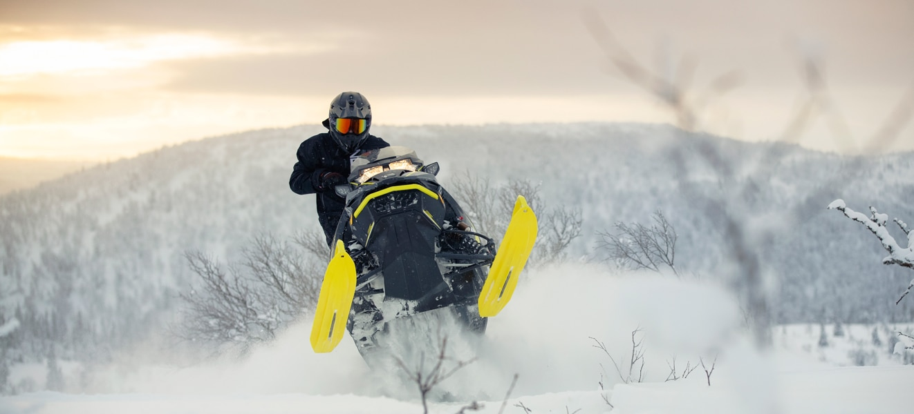 A man is jumping with his Lynx Xtrim Snowmobile Model on the top of a snowy hill