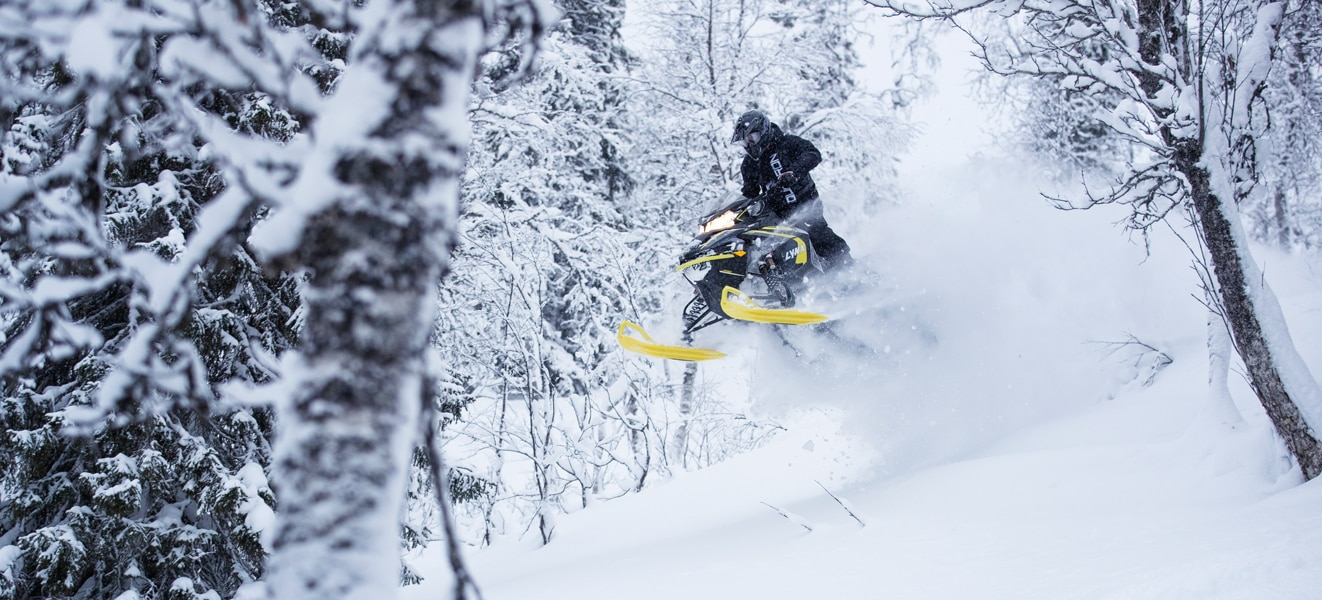 A man is jumping with his Lynx Xtrim Snowmobile Model in the snowy forest