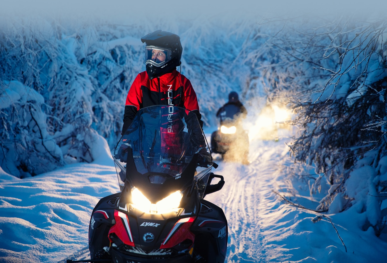 A group of drivers follow a snowy path in the forest with their Lynx Xtrim Snowmobile Model