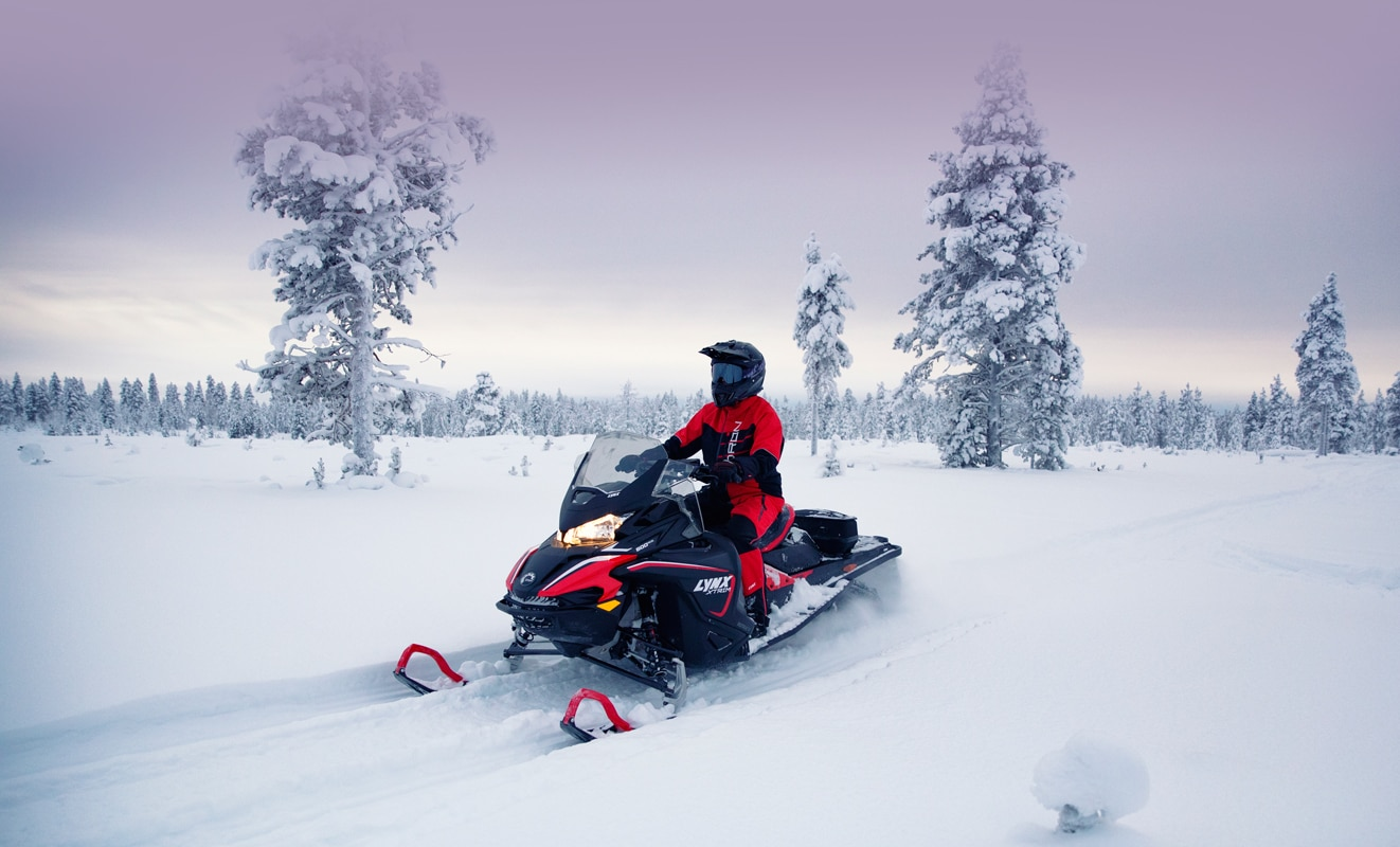 A man is riding his Lynx Xtrim Snowmobile Model on a snowy road
