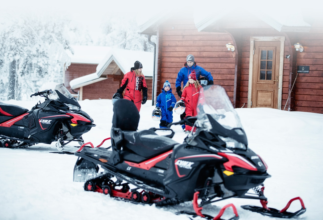 A family of 4 people are heading towards their 2 Lynx Xtrim Model Snowmobile