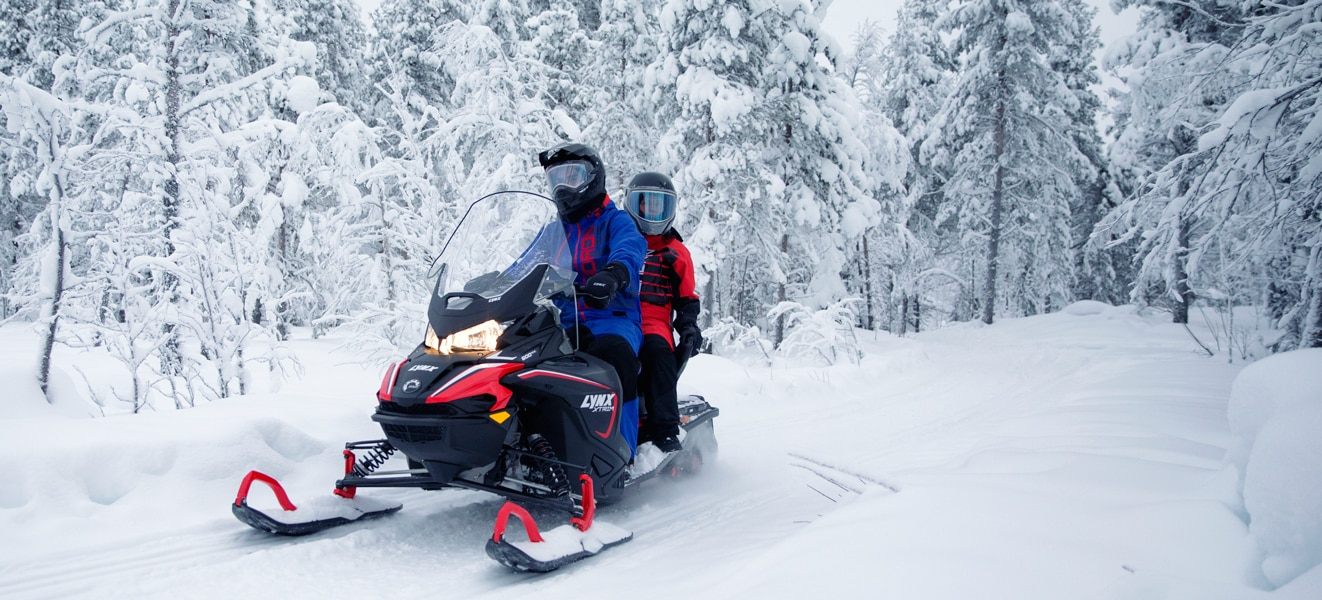 A couple is riding in the middle of a snowy forest on their Lynx Xtrim Snowmobile Model
