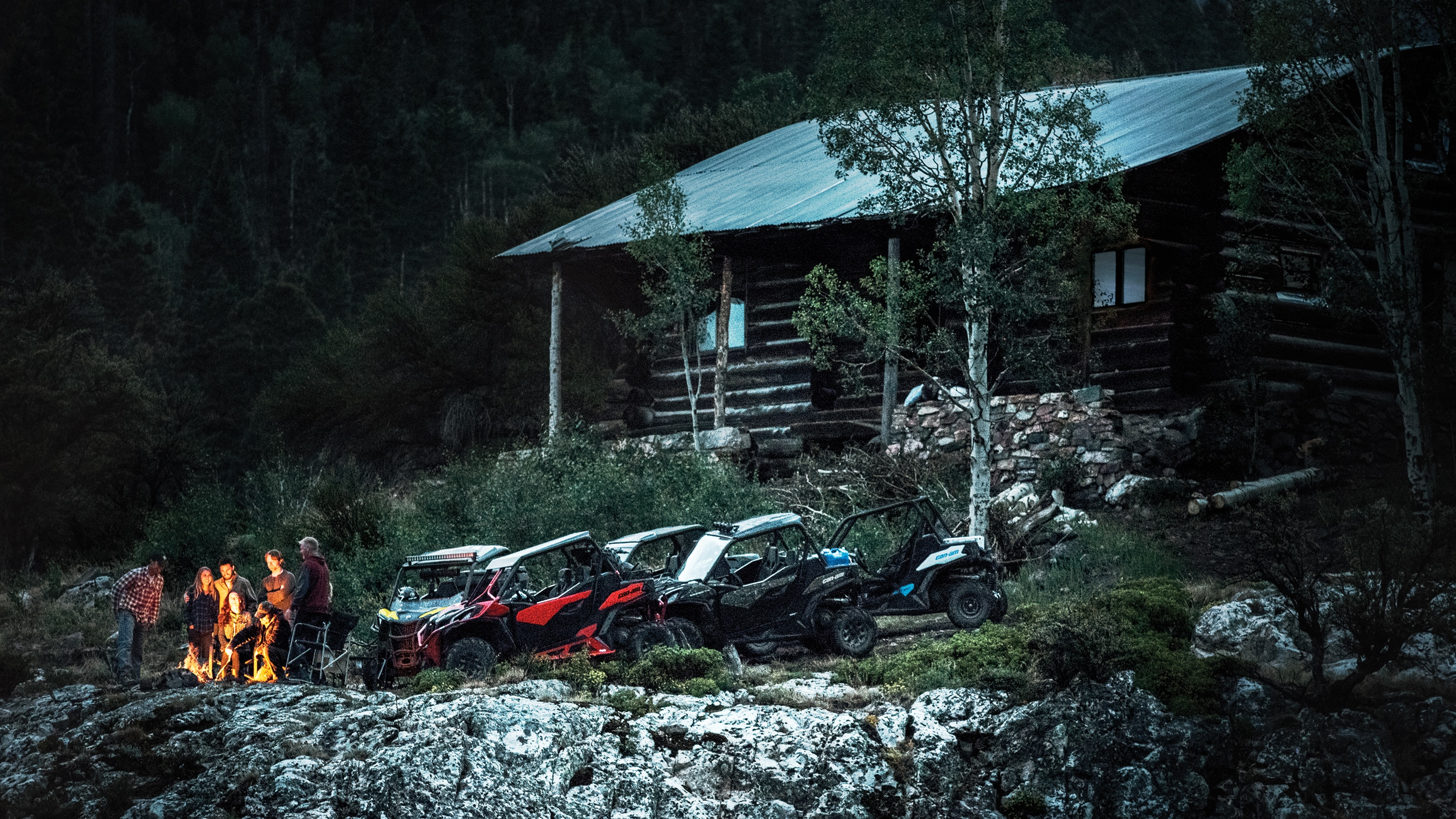 Friends near their Maverick Trail models close to a cabin in the woods