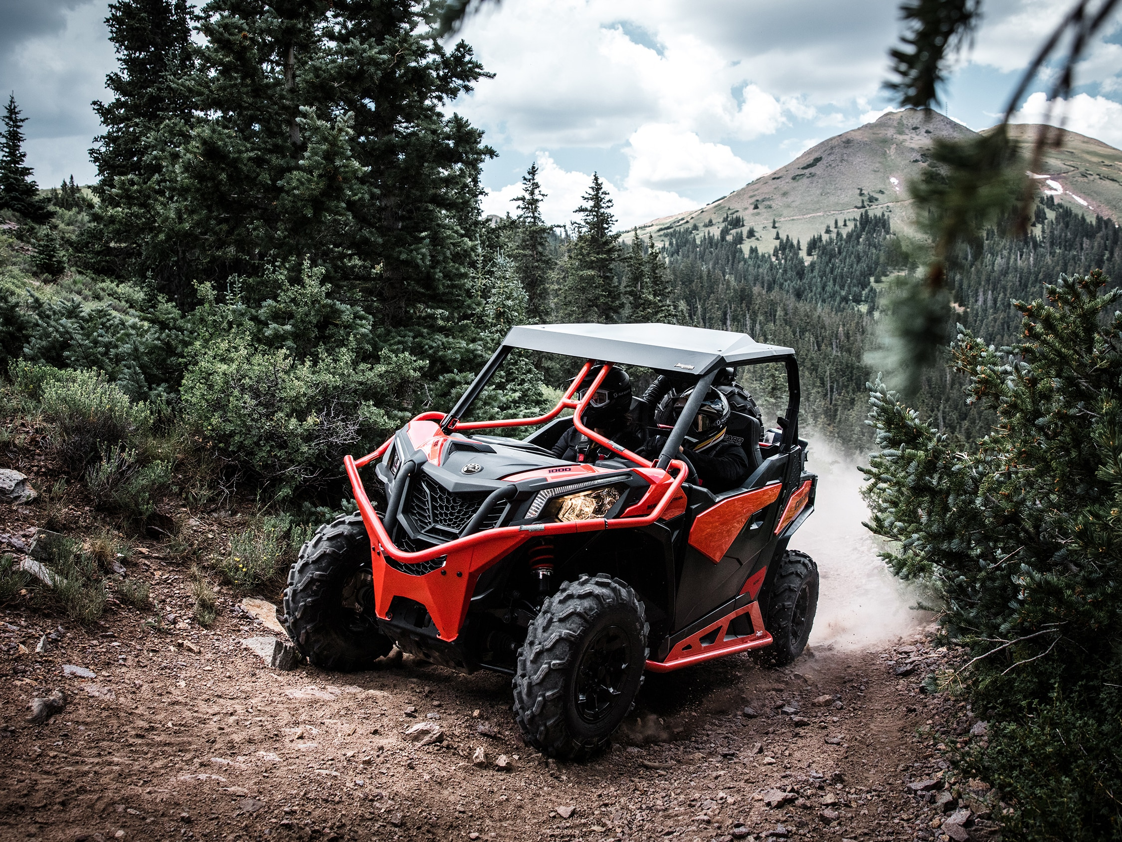 Man driving a Maverick Trail up a forest trail