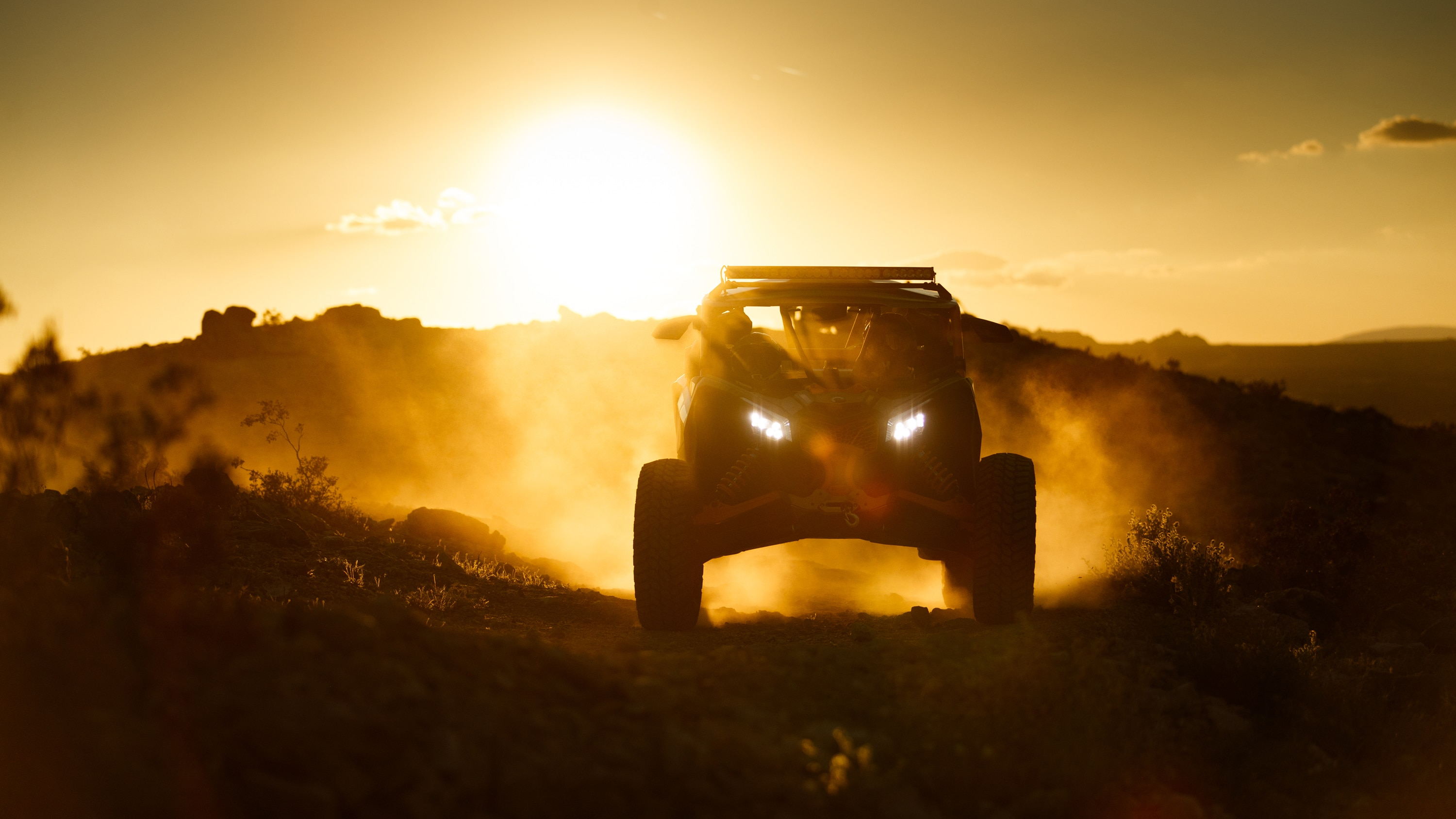 Maverick driving down a cliff with the sunset behind