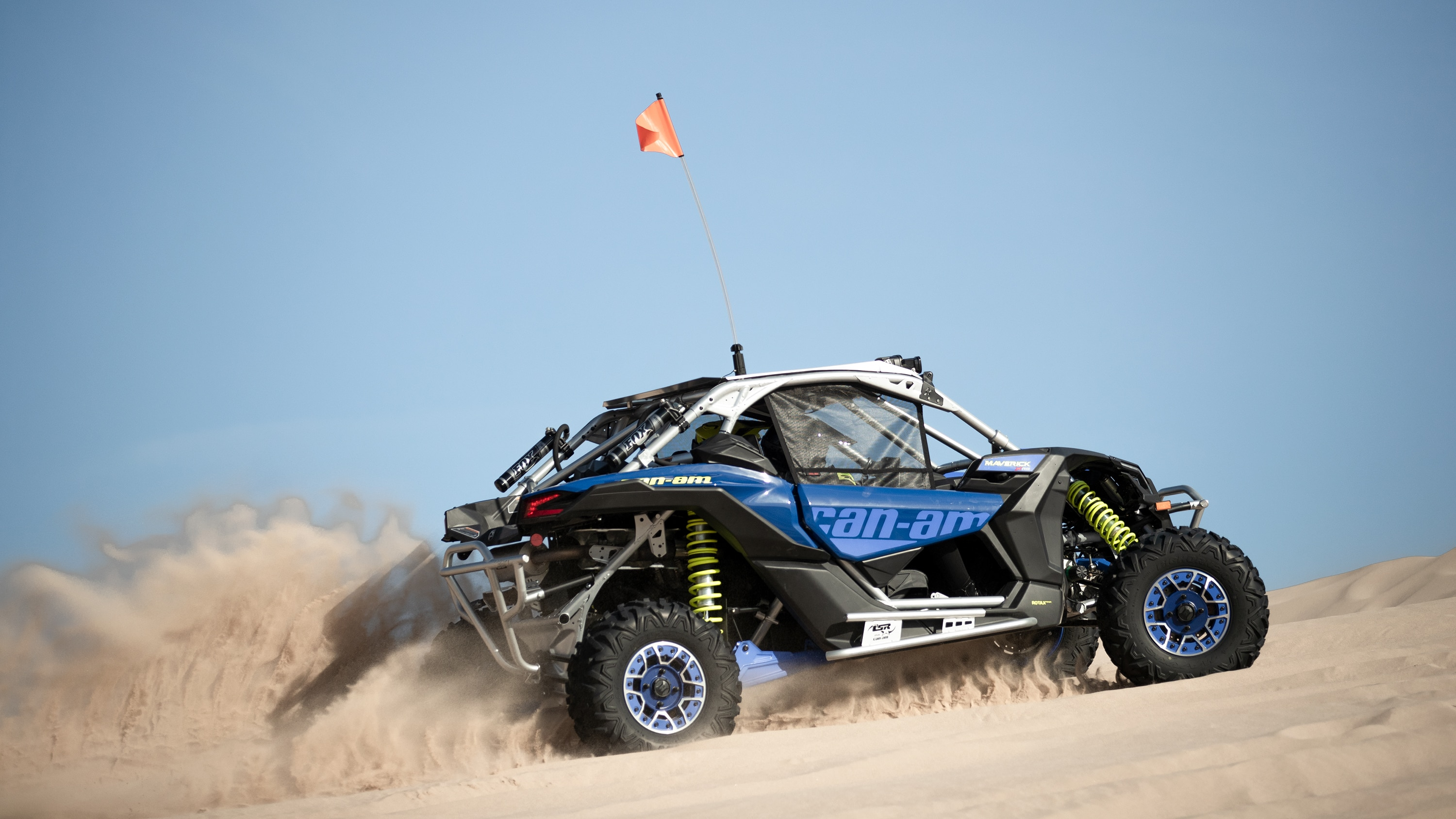 A single Maverick driving up a dune