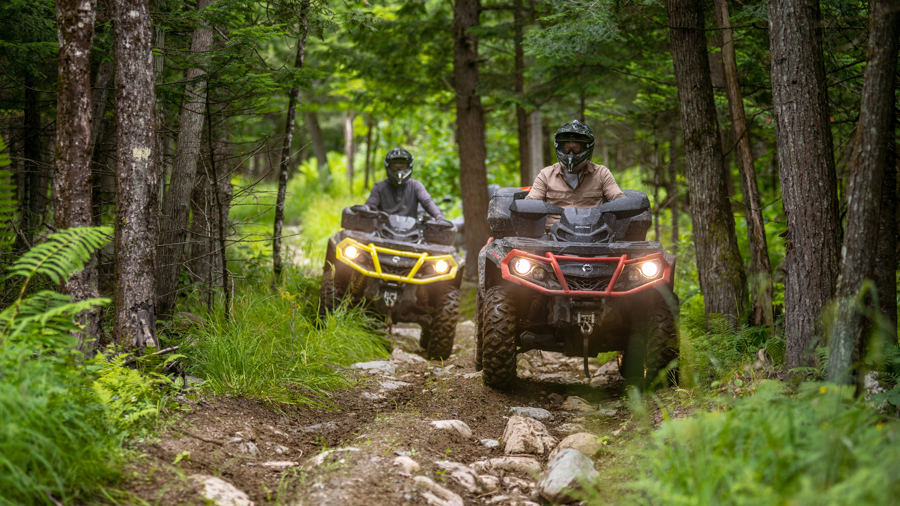 Two men driving their Outlander ATV through a forest trail