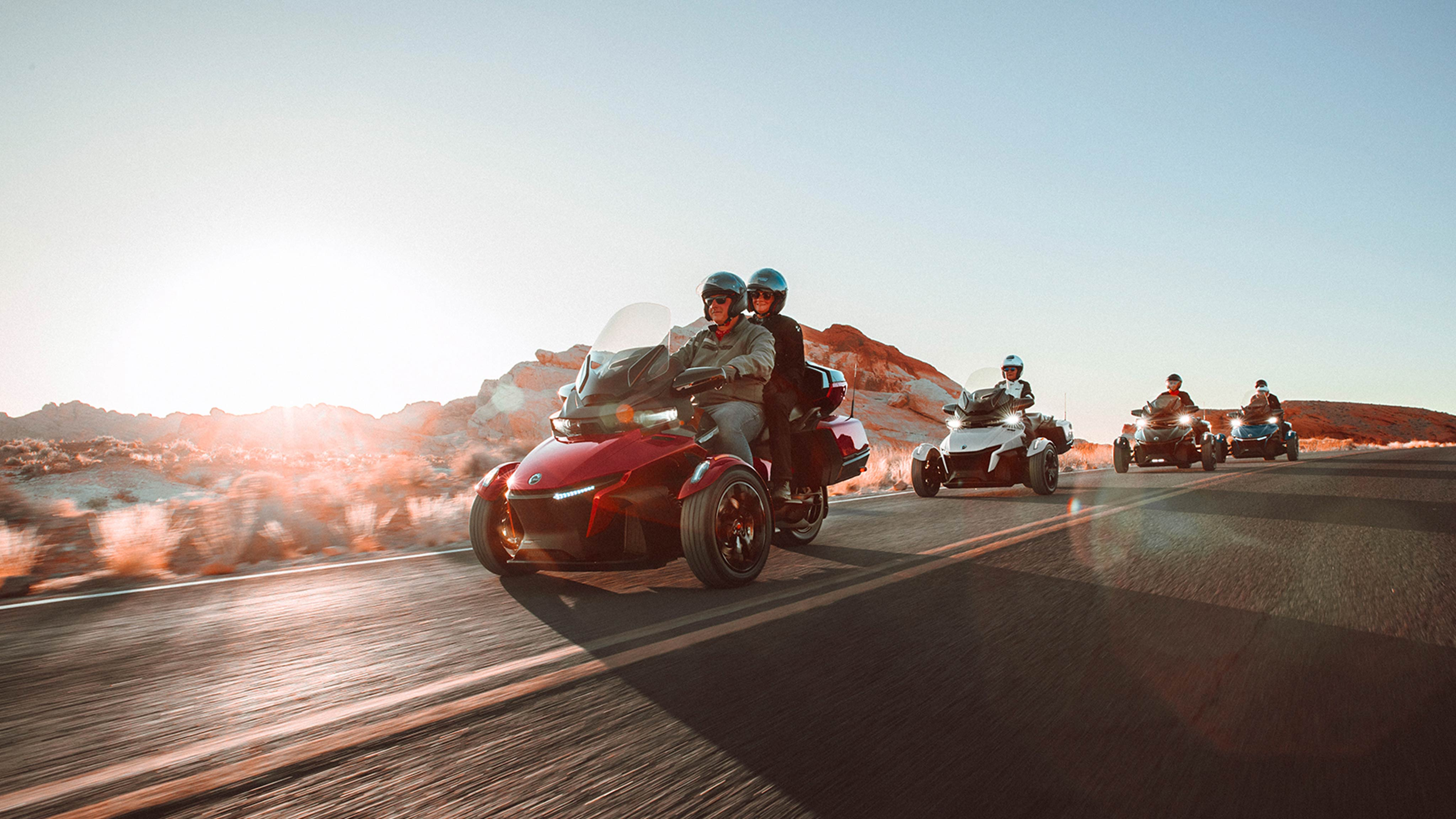 Group of people riding four Can-Am Ryker vehicles on a scenic road