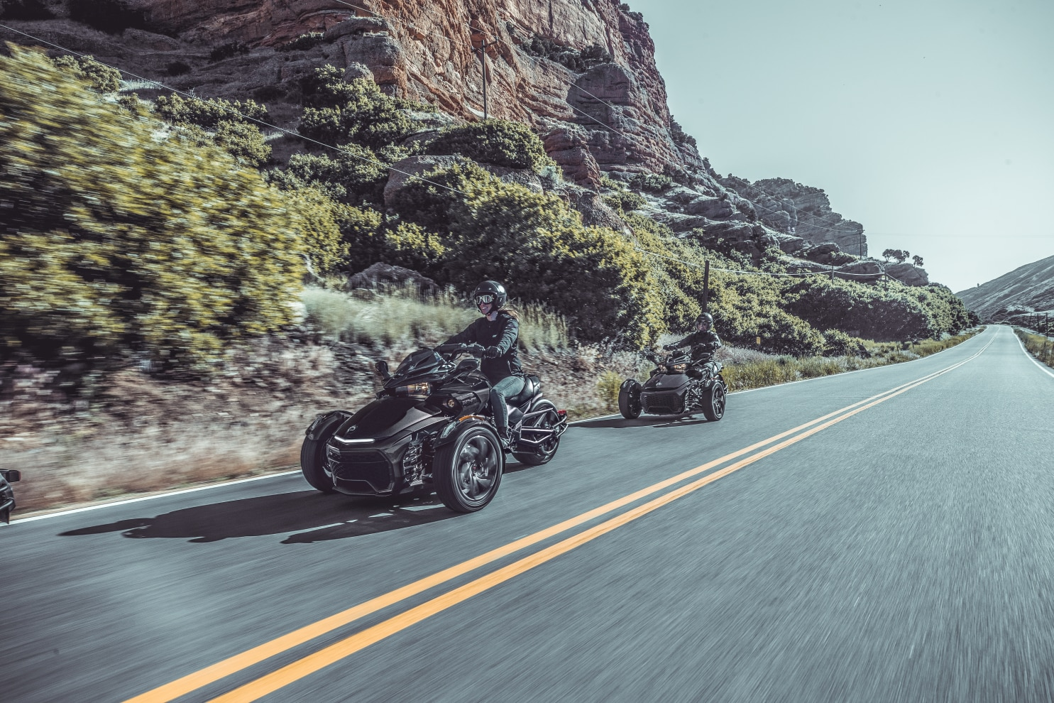 Two people driving their Spyder F3 on a scenic route