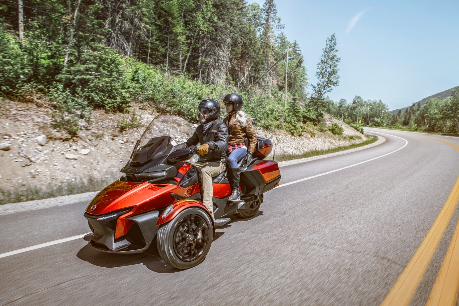 Right angle view of a couple driving a Can-Am Spyder RT on a scenic road