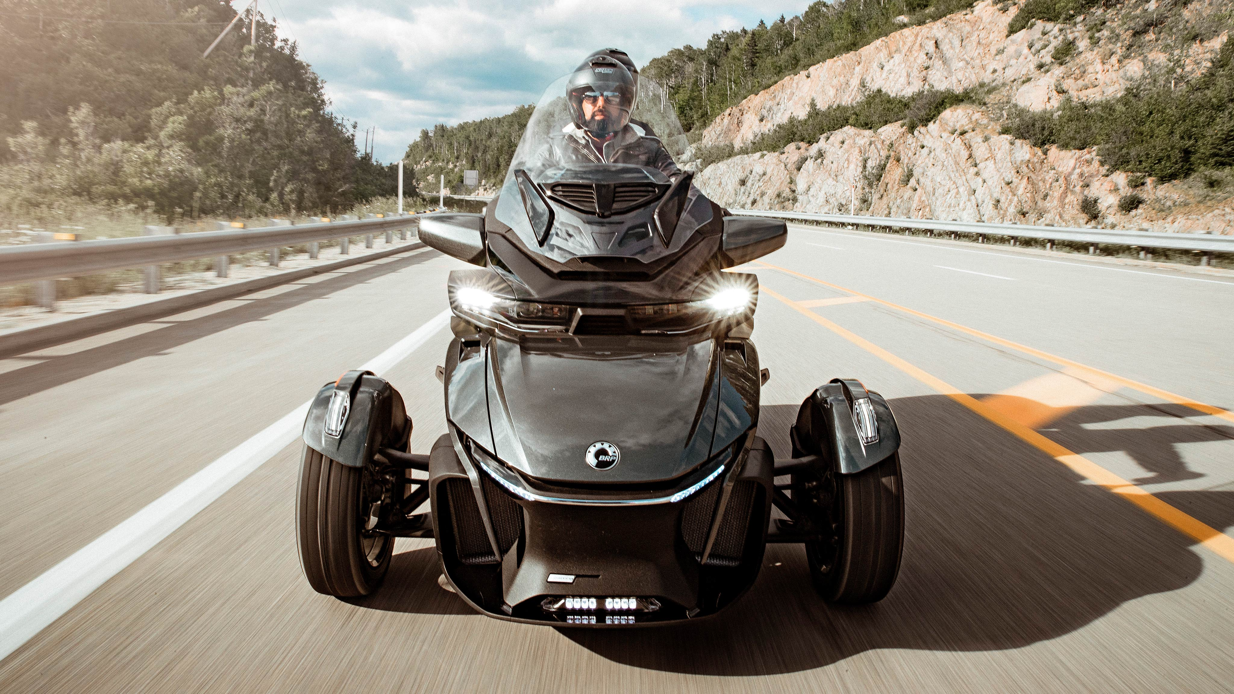 A couple driving a Can-Am Spyder RT on the road