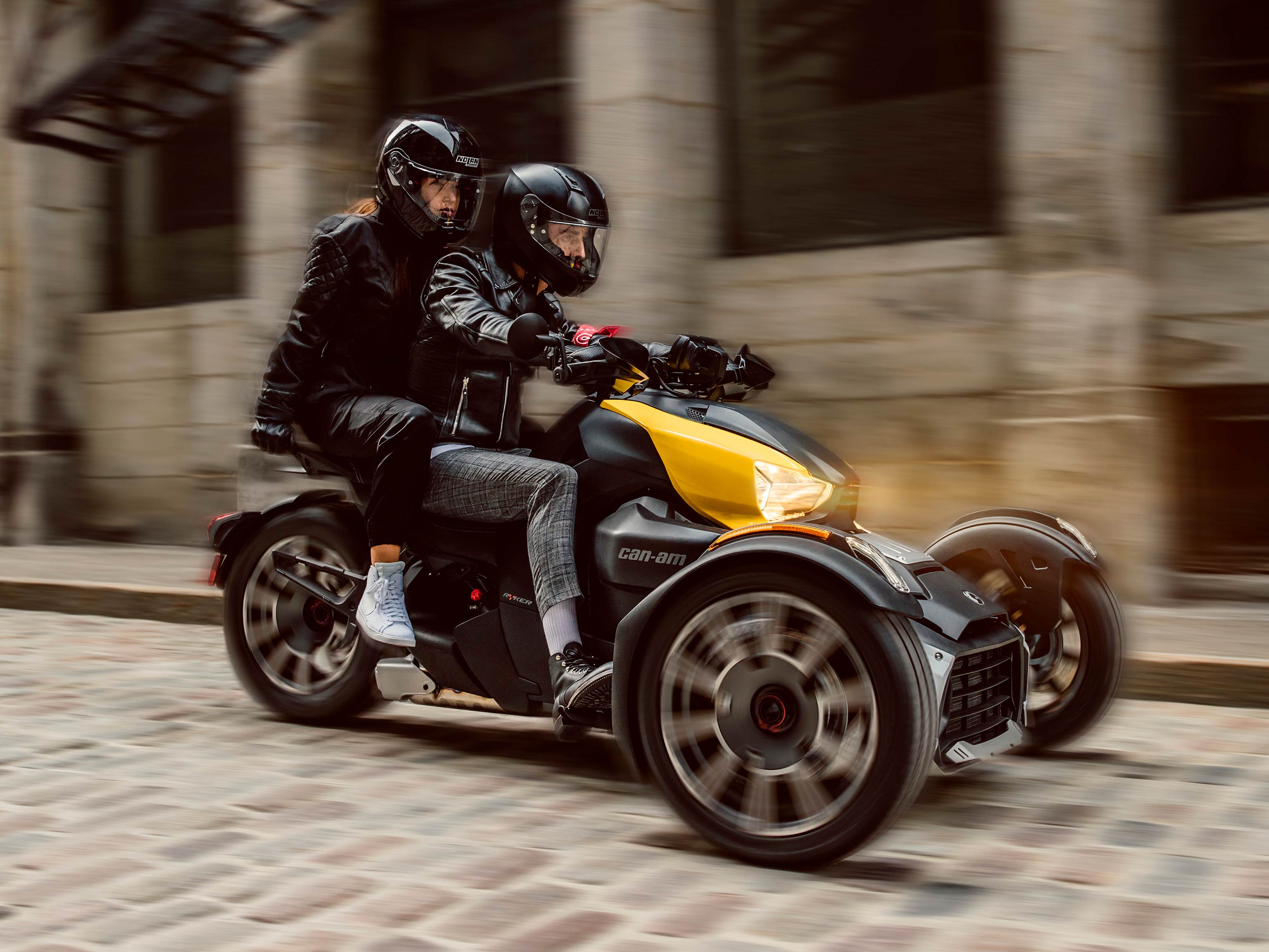 A couple riding a Can-Am Ryker with yellow shock panels along a cobblestone street