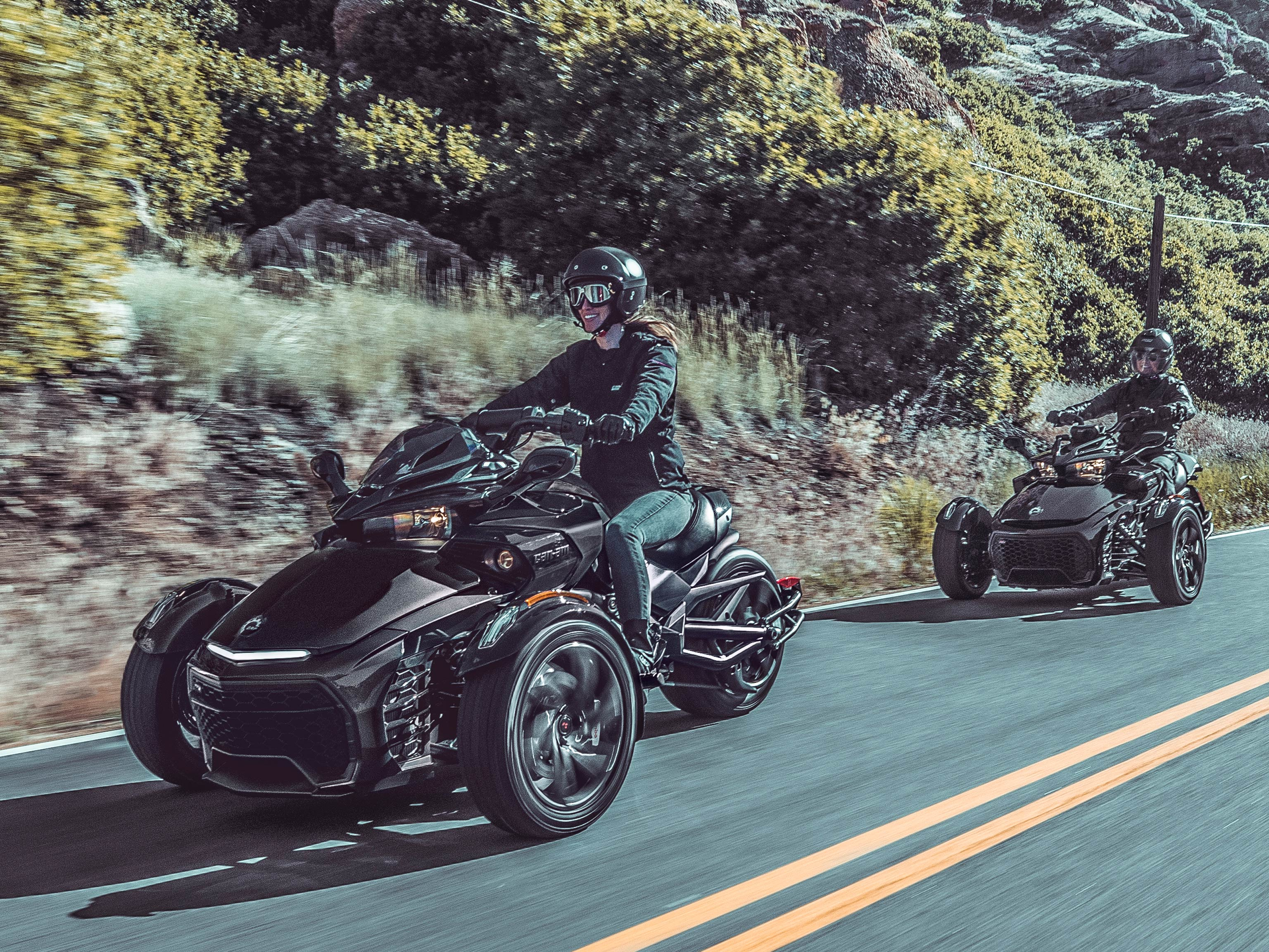 Two people riding Can-Am Spyder vehicles along an open desert road