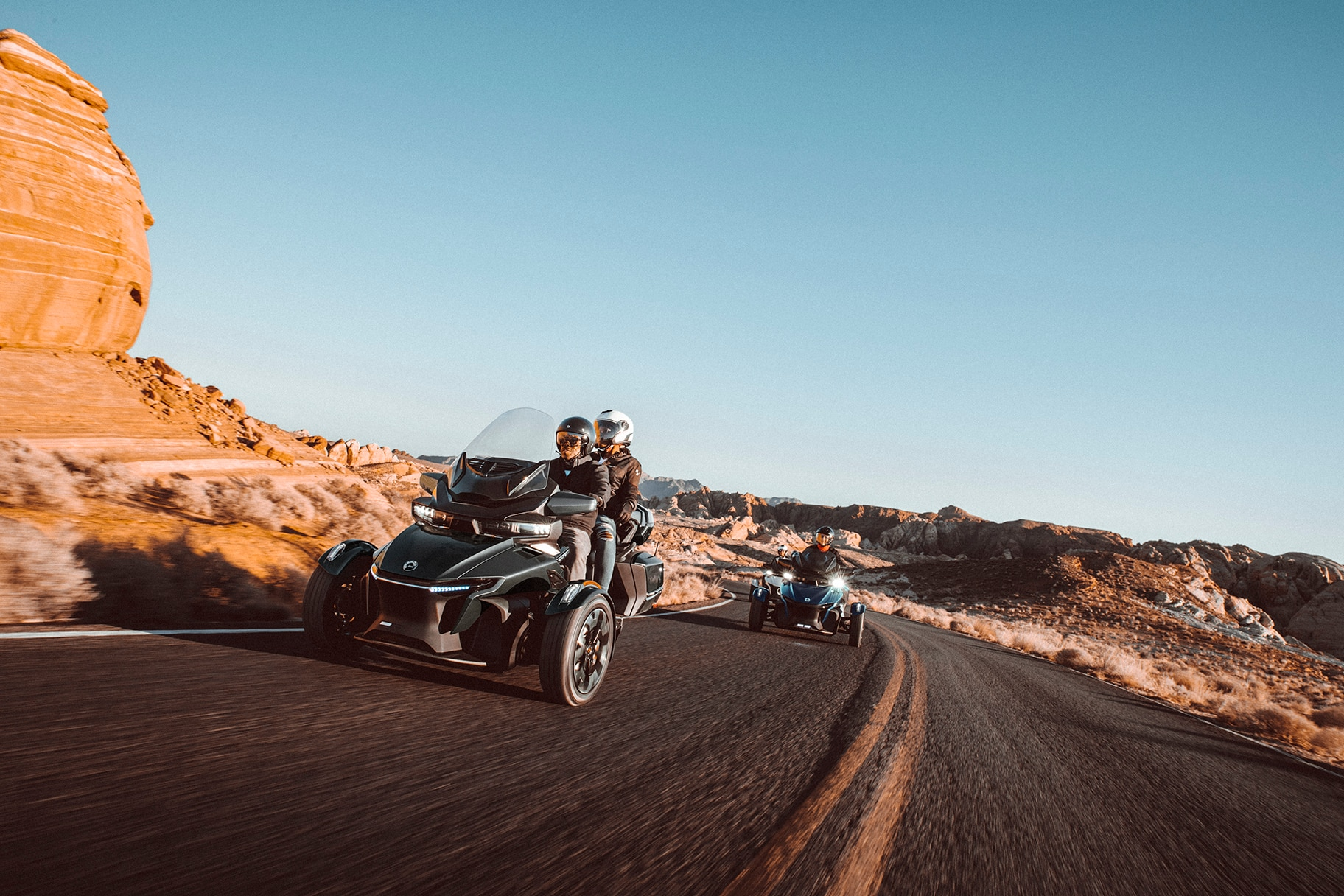 A couple ride their Spyder RT on the road