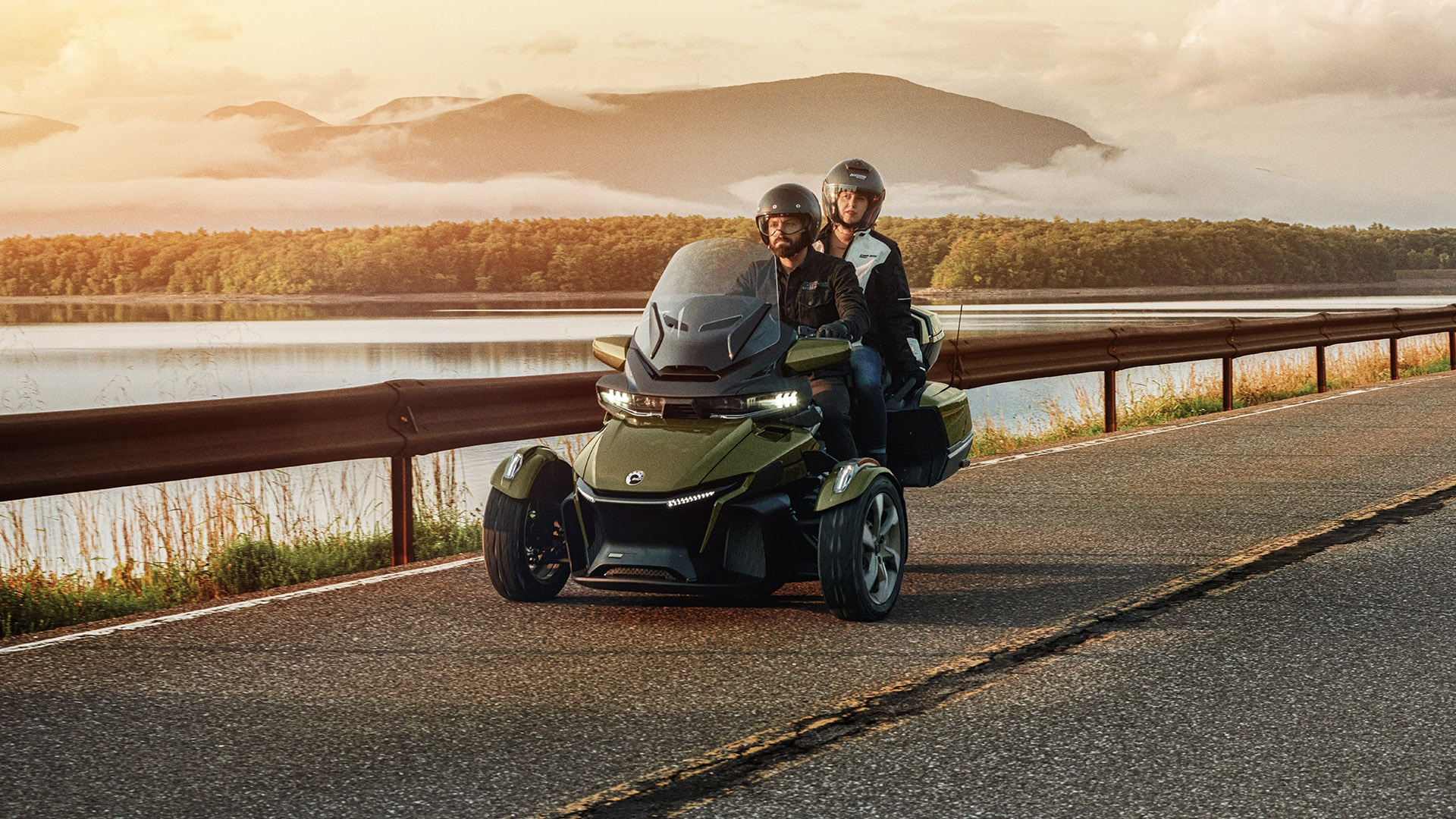 A man and a woman riding Can-Am Spyder 2021 near the lake