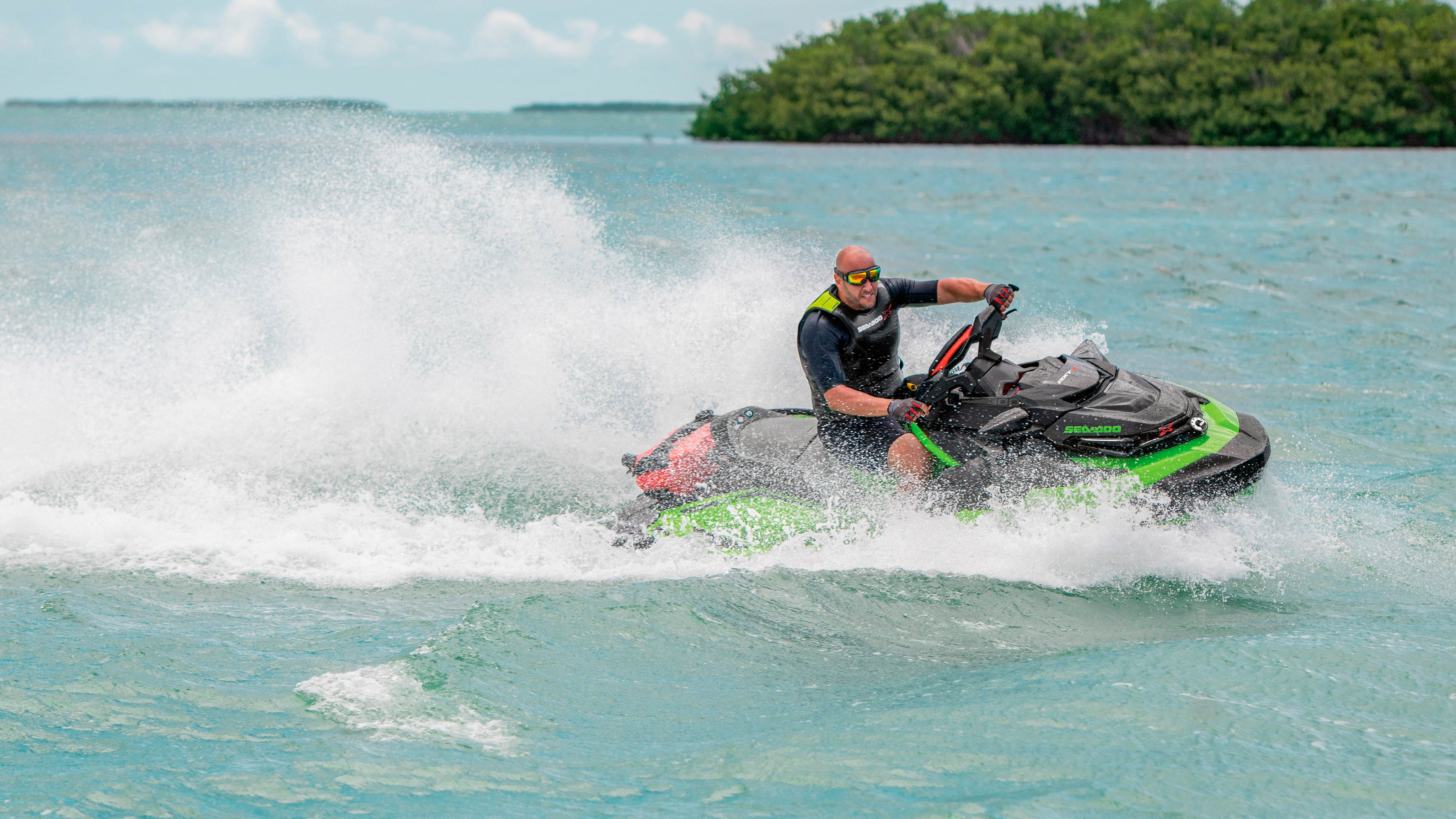 Man riding his Sea-Doo RXT-X next to a patch of land