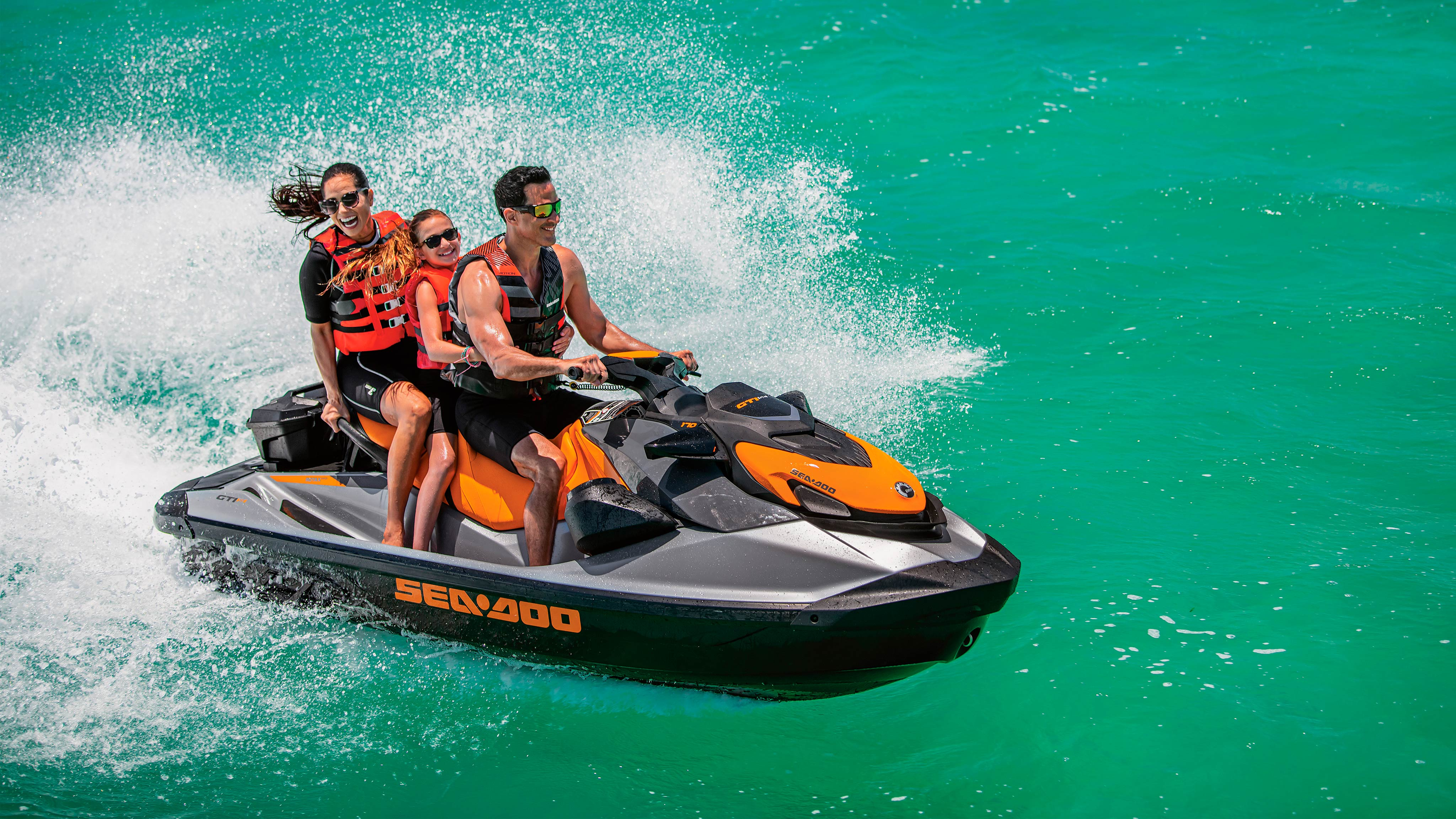 Three people riding a Sea-Doo GTI SE in the water