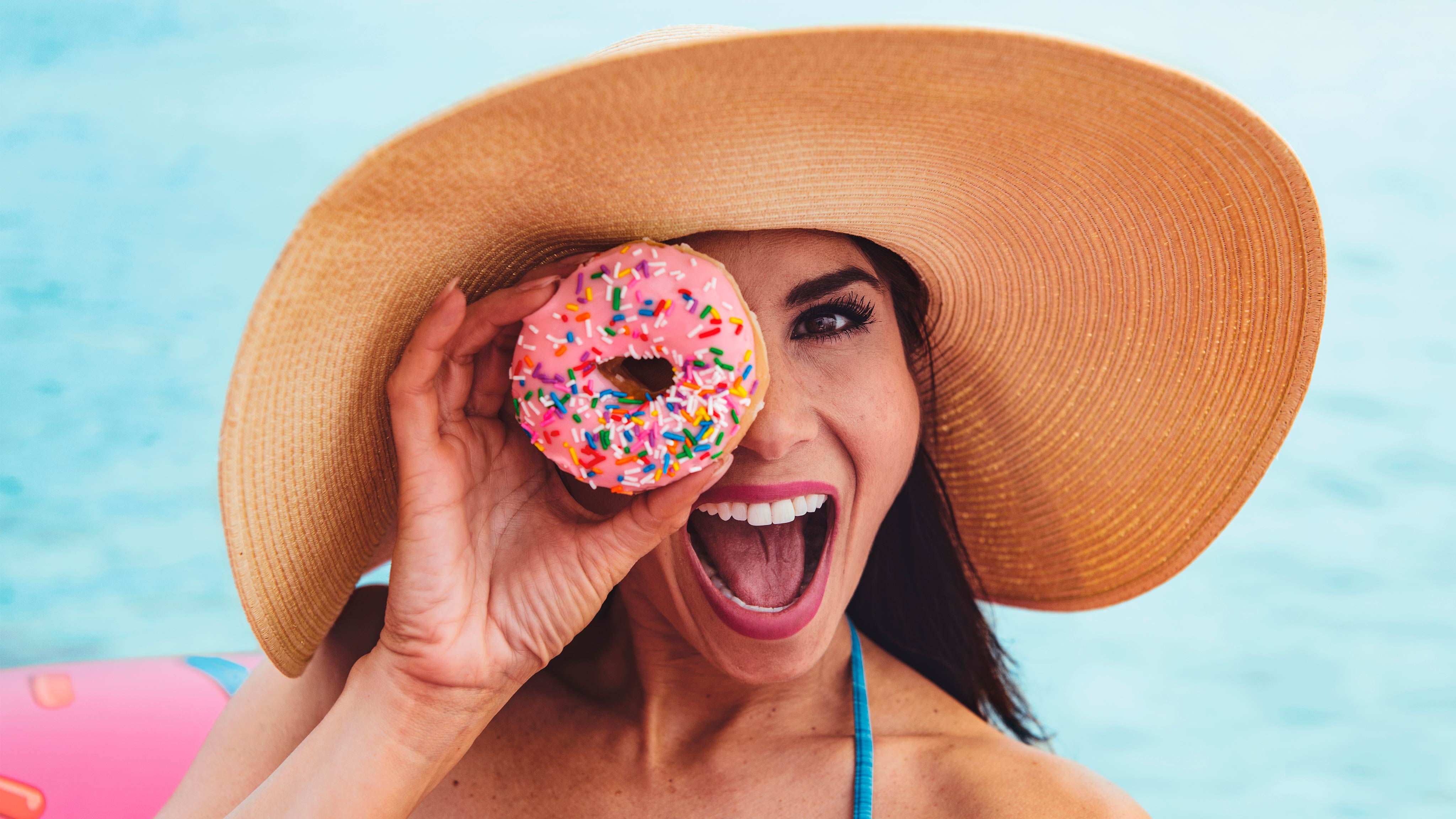 Woman smiling while holding a donut