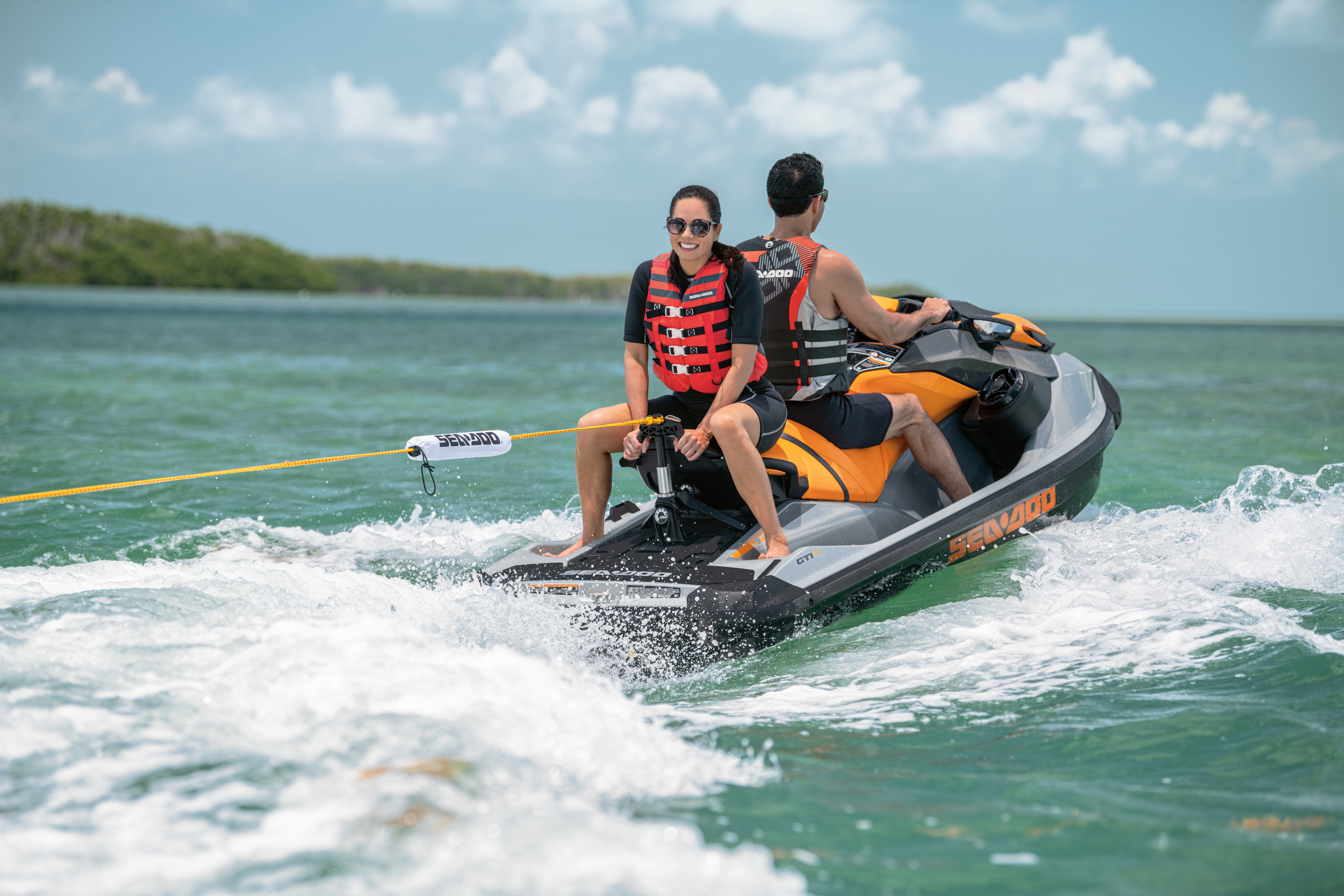 Man and woman pulling a tube from their Sea-Doo GTI-SE