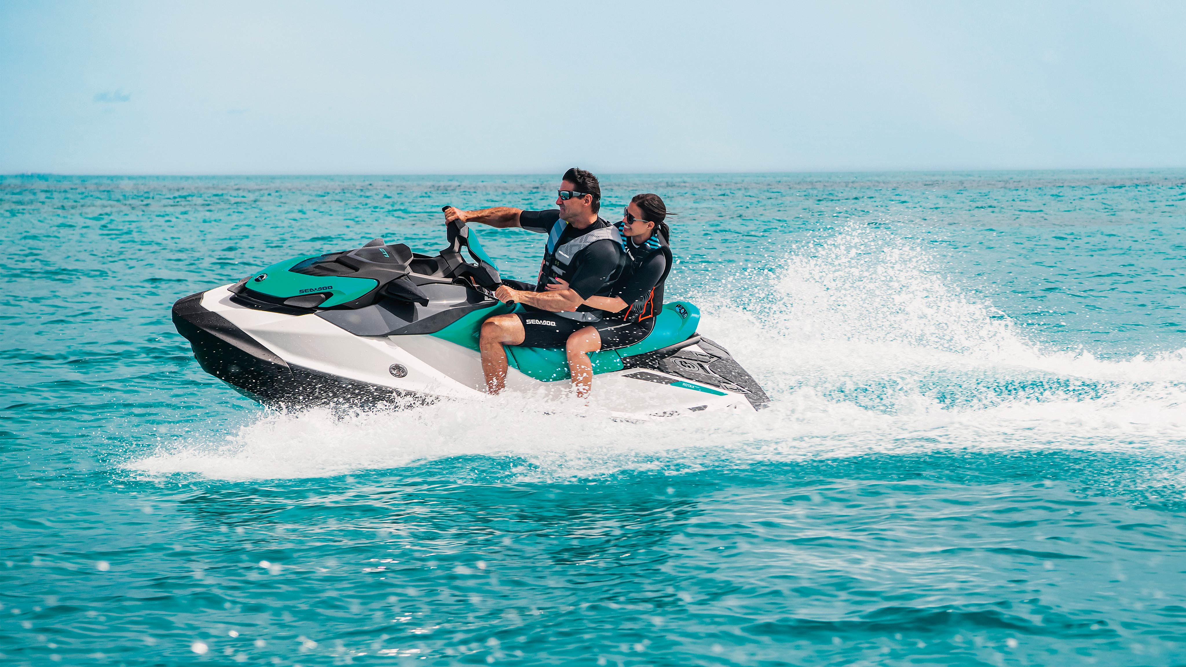 A man and a woman riding a Sea-Doo GTI