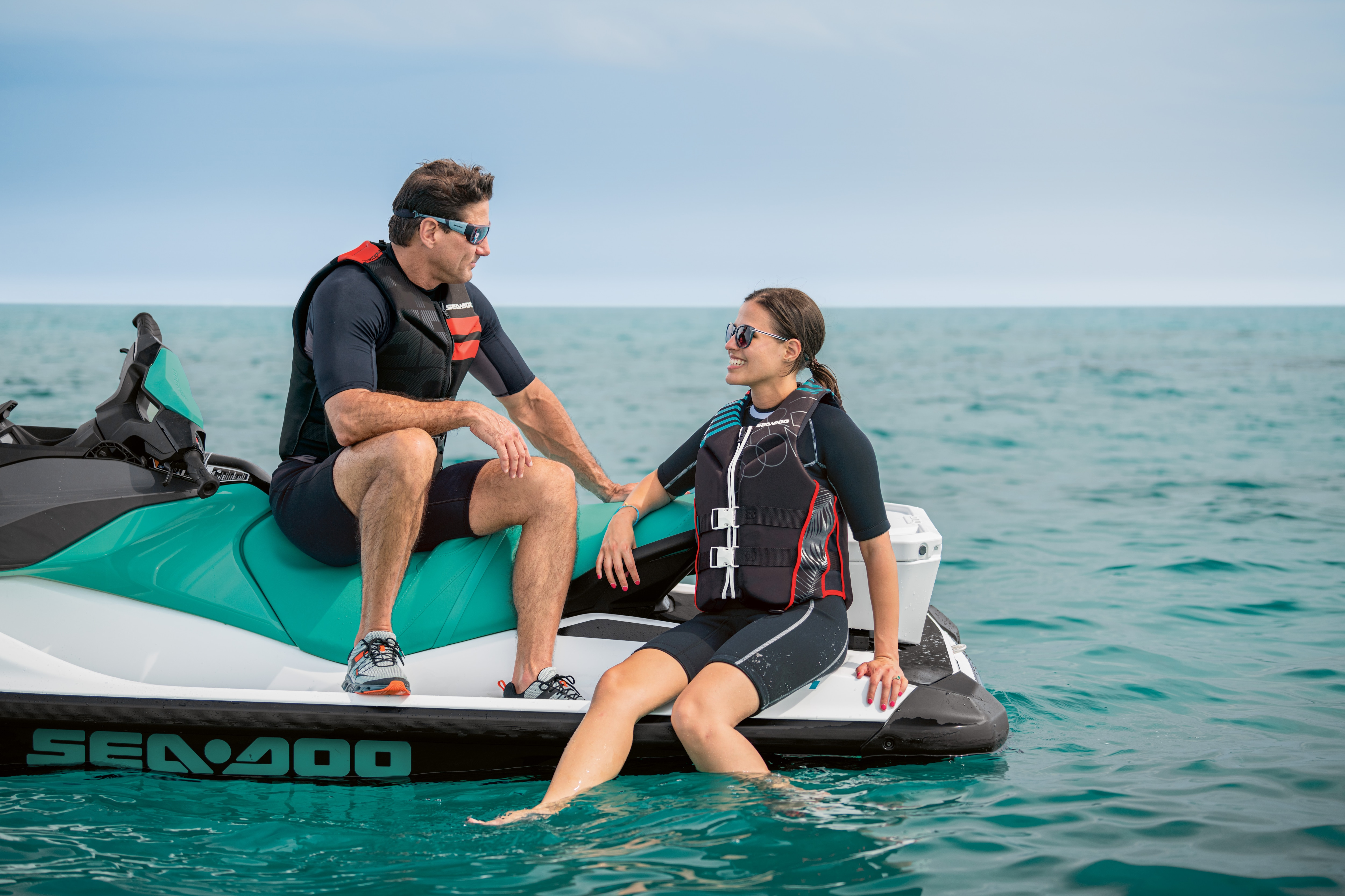 Man and woman sitting on a Sea-Doo GTI parked in the water