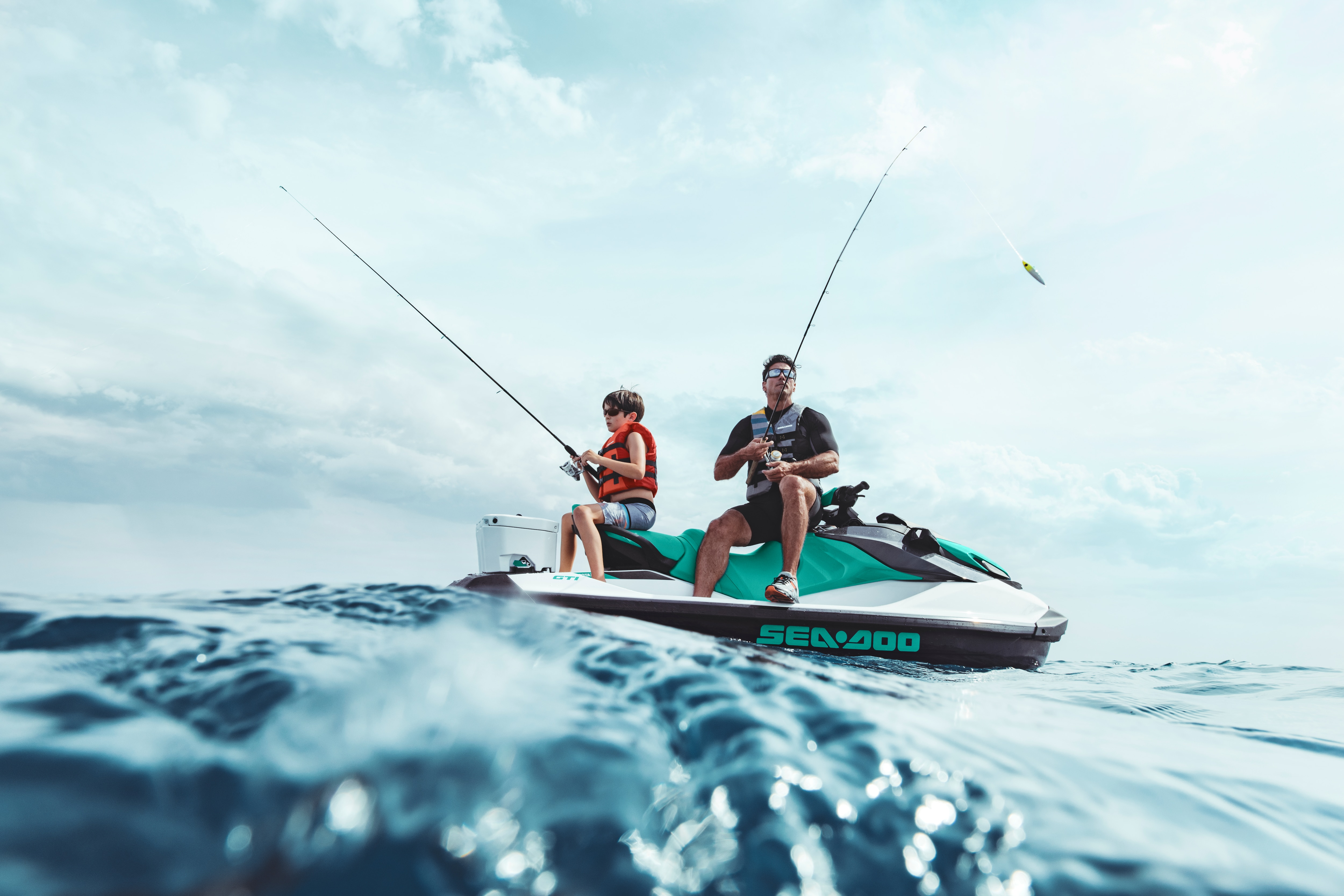 Man and kid fishing while sitting on a Sea-Doo GTI