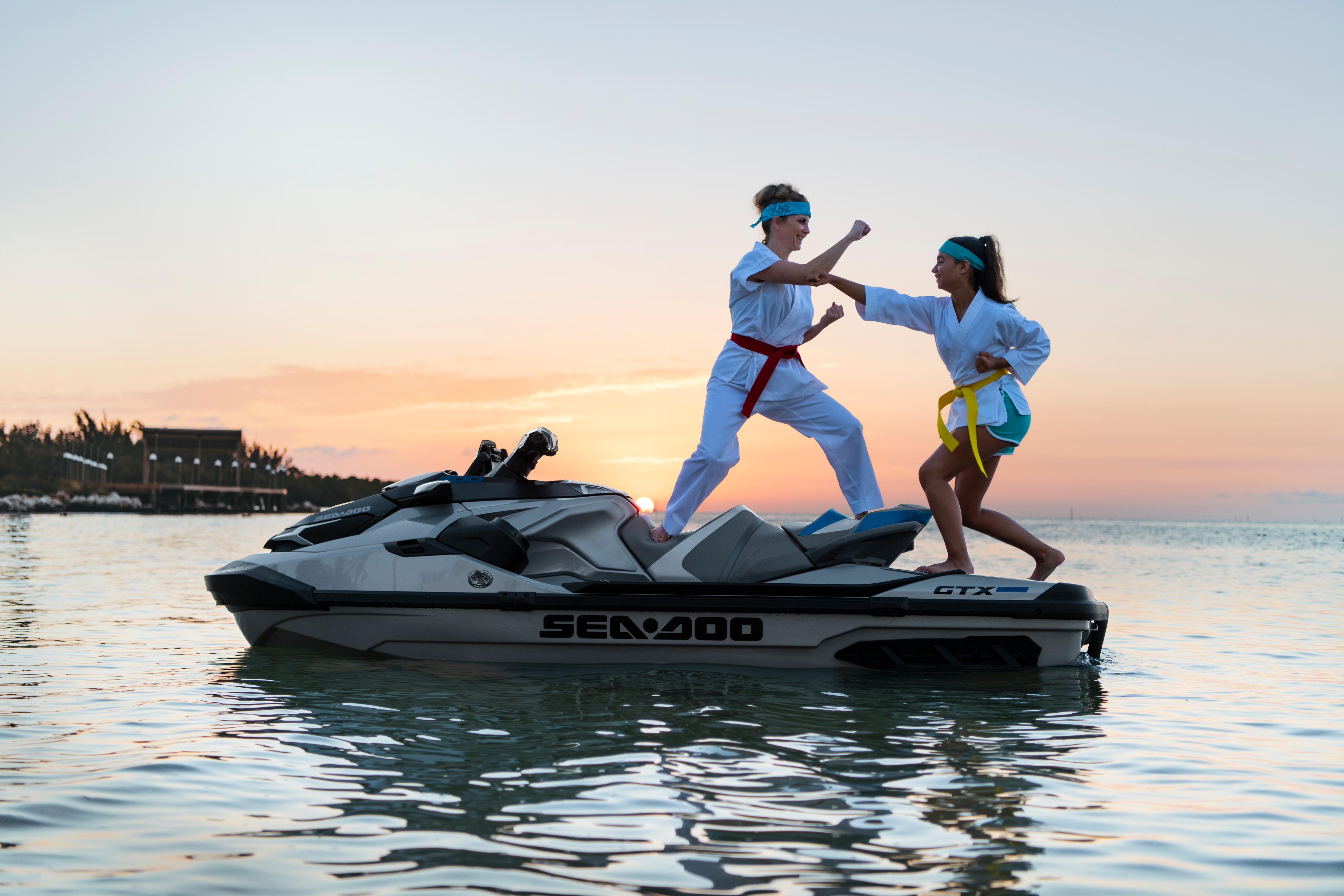 Two women doing karate while standing up on a Sea-Doo GTX Limited