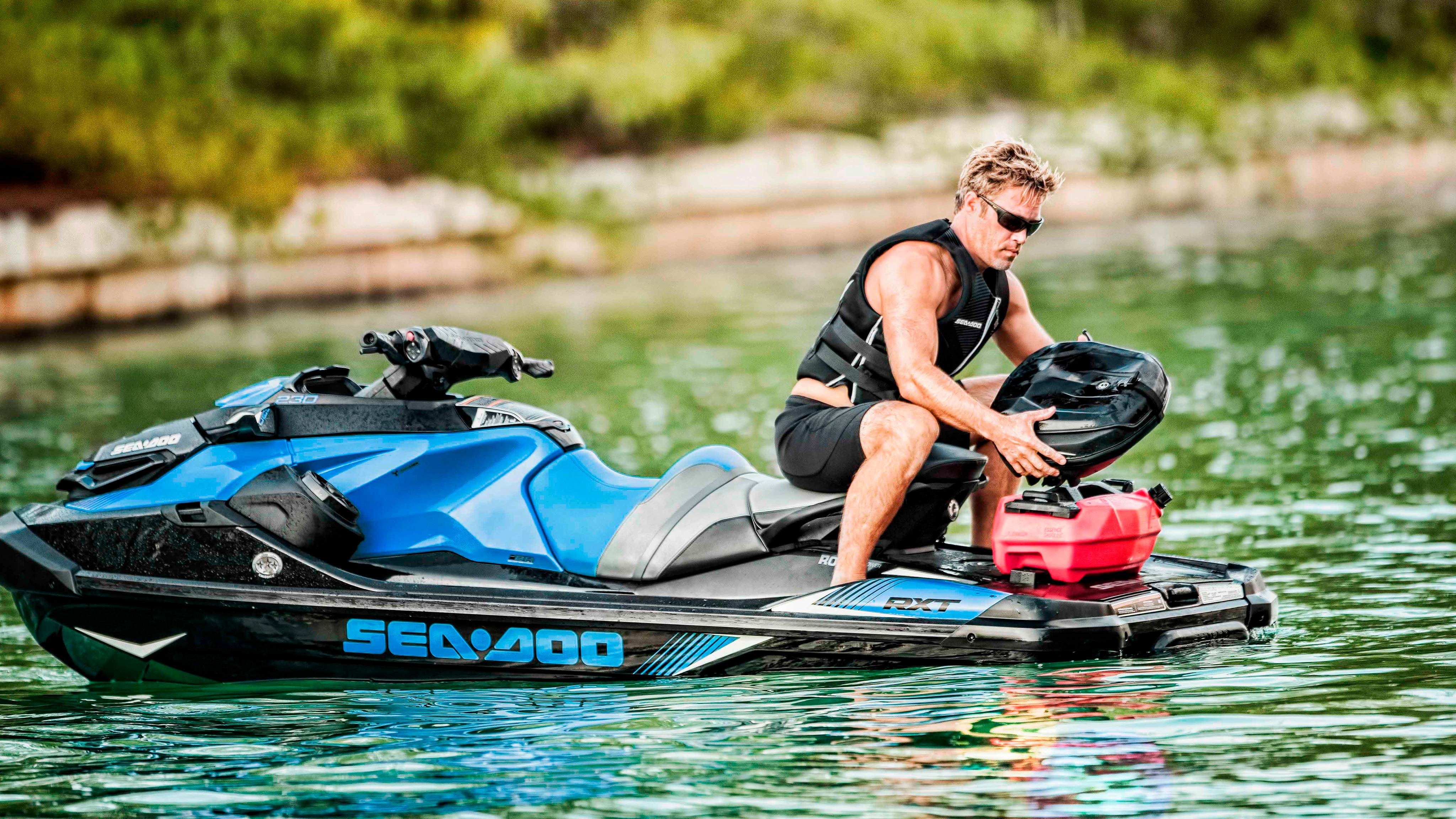 Man holding a Sea-Doo accessory on the back of his GTX
